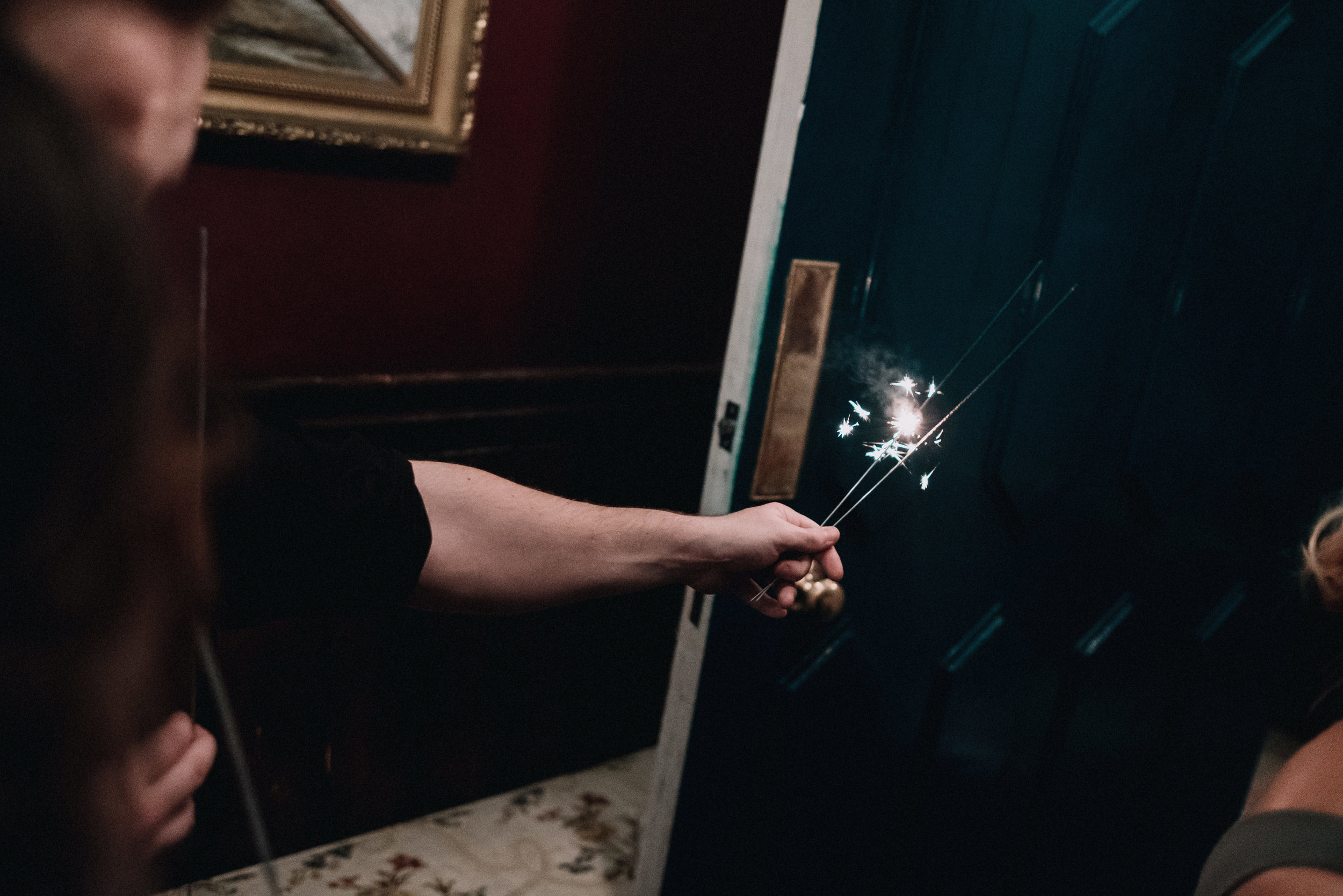 Woman holds a lit sparkler with an outstretched arm