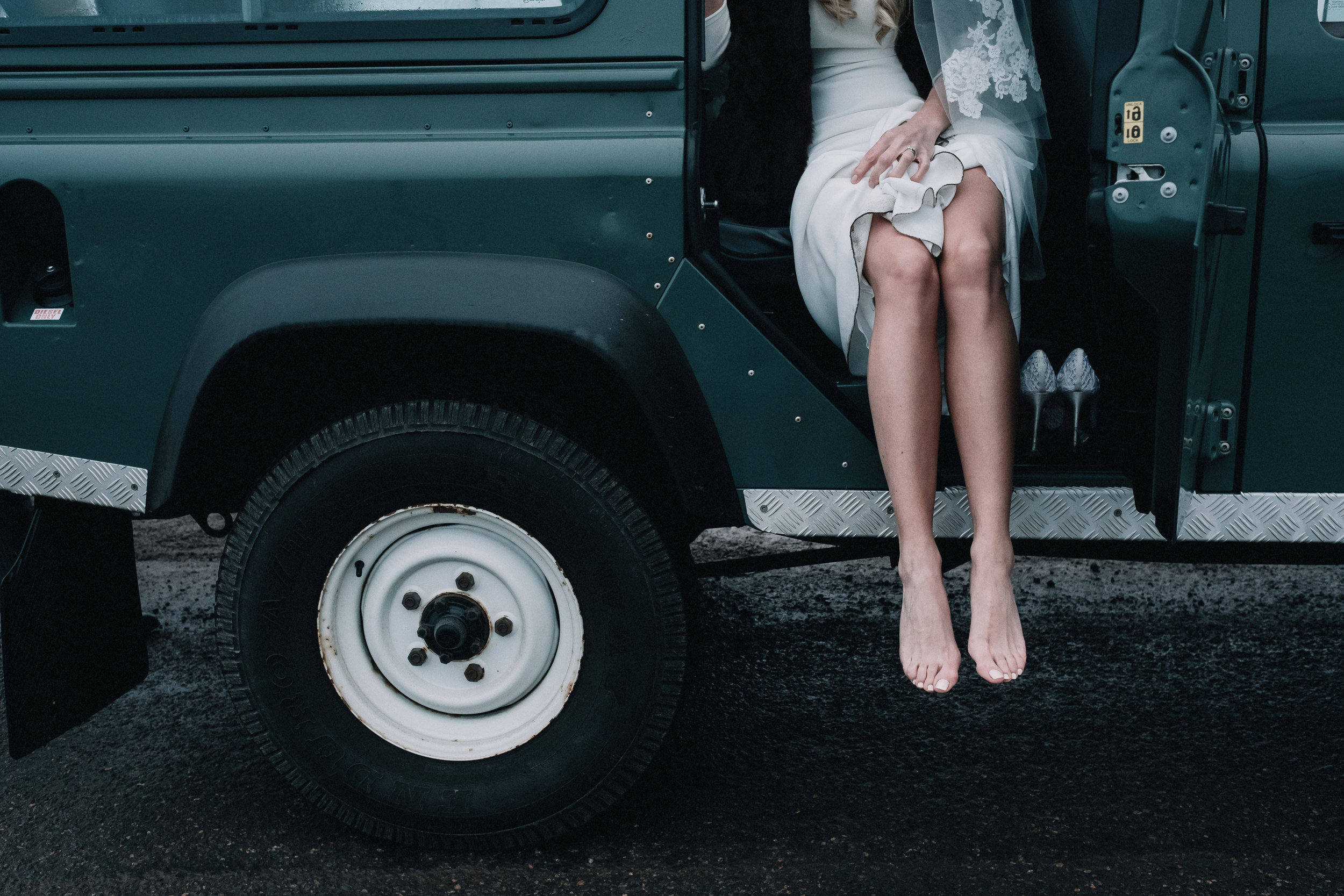 A bride sits without shoes in the passenger seat of a Land Rover Defender