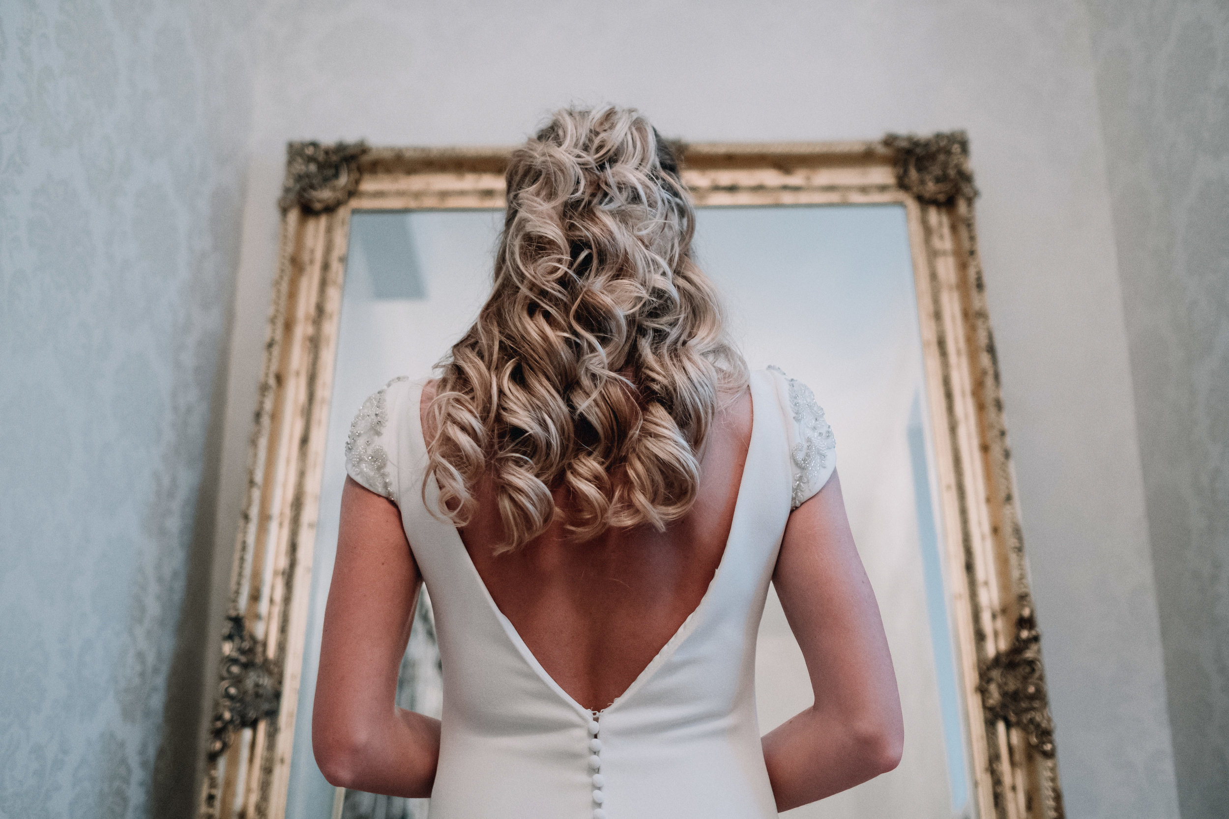 Bride looking at herself in a mirror