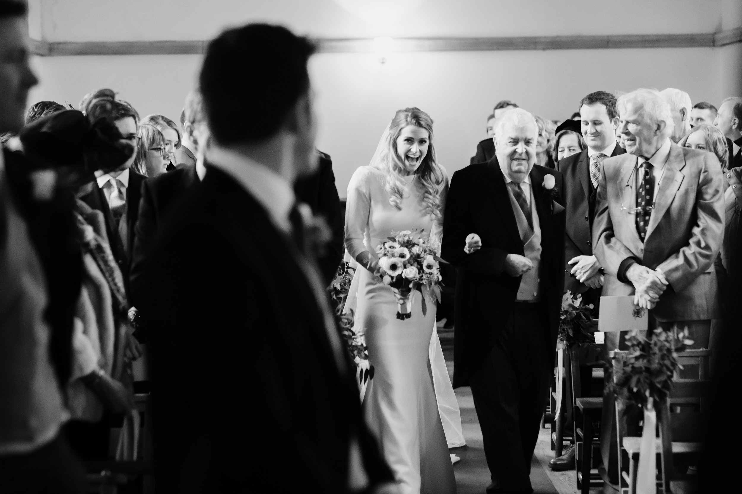 Bride with beaming smile as she walks down the aisle