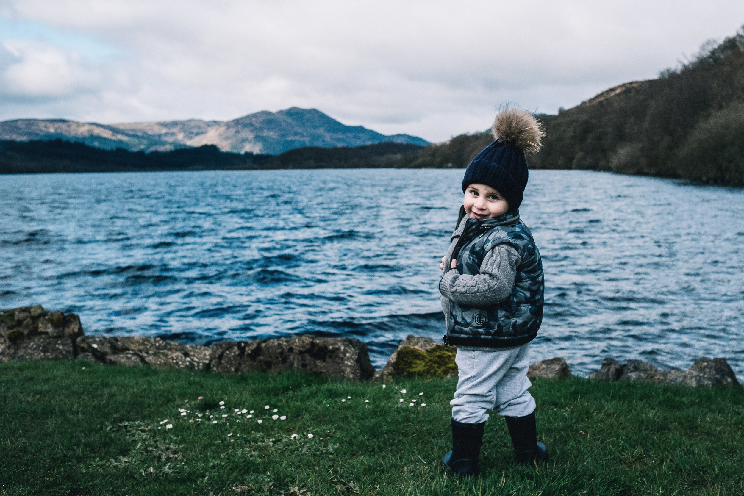 Young boy stands by Loch Venachar