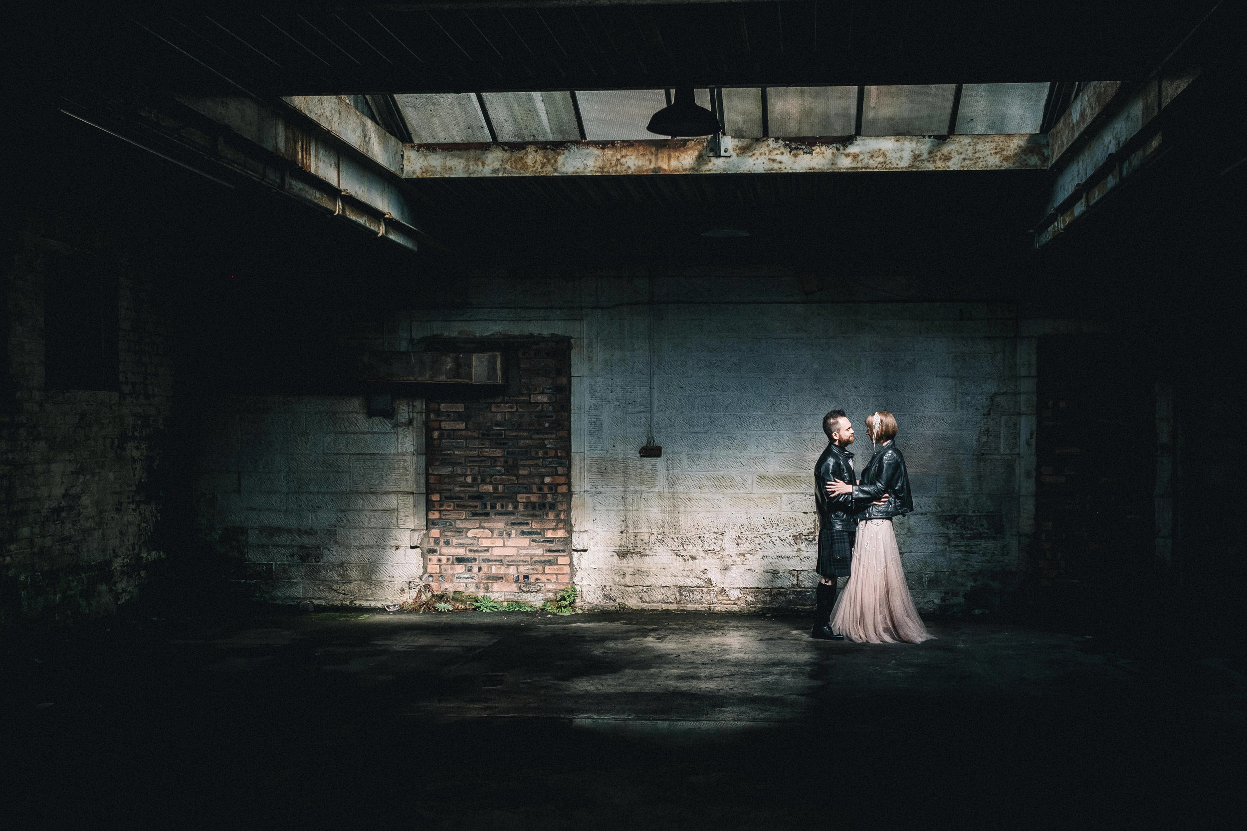 Couple standing in a shard of light