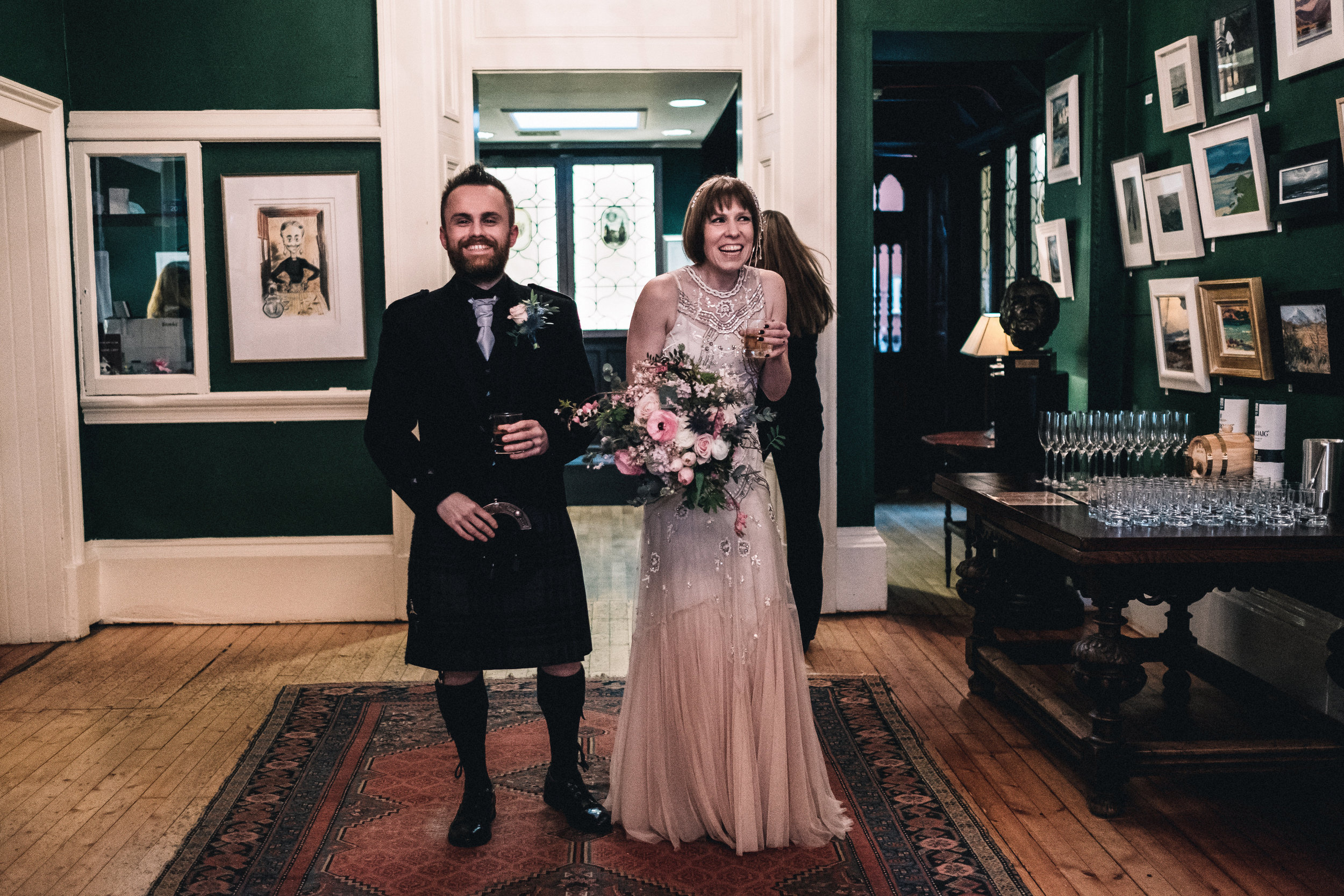 Bride and groom beaming at their guests