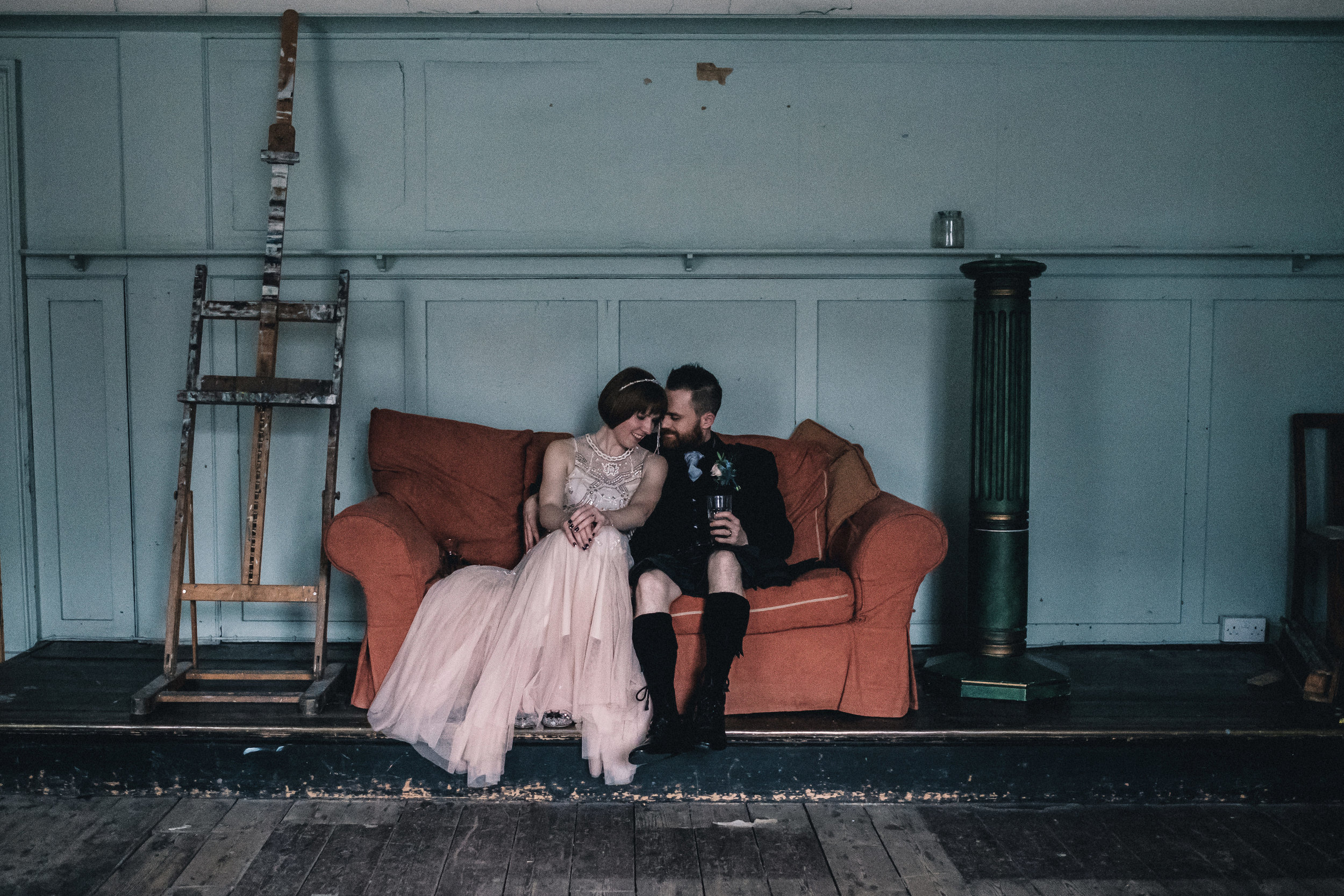 Bride and groom sit close on a sofa