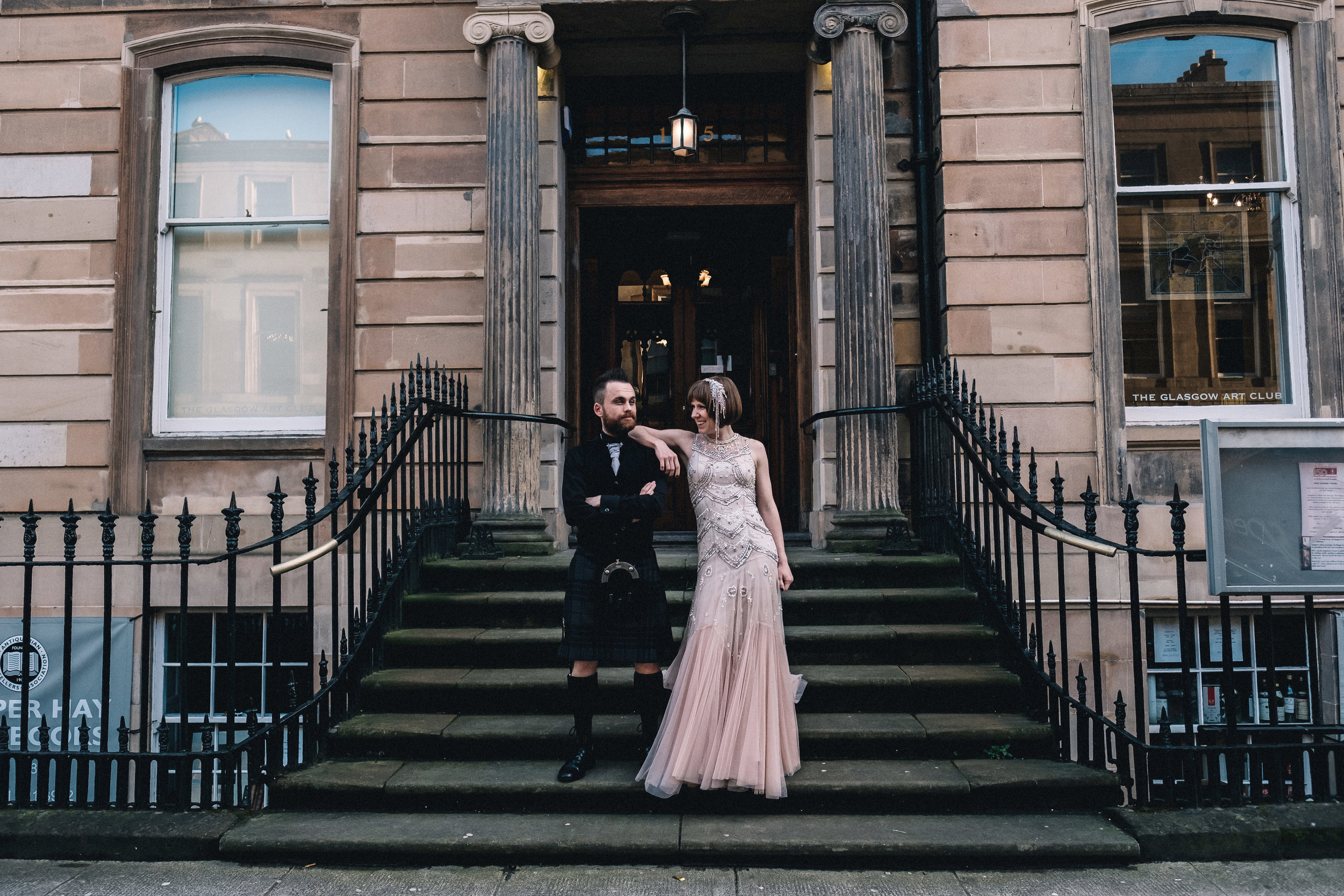 Couple stand on stairs of The Glasgow Art Club
