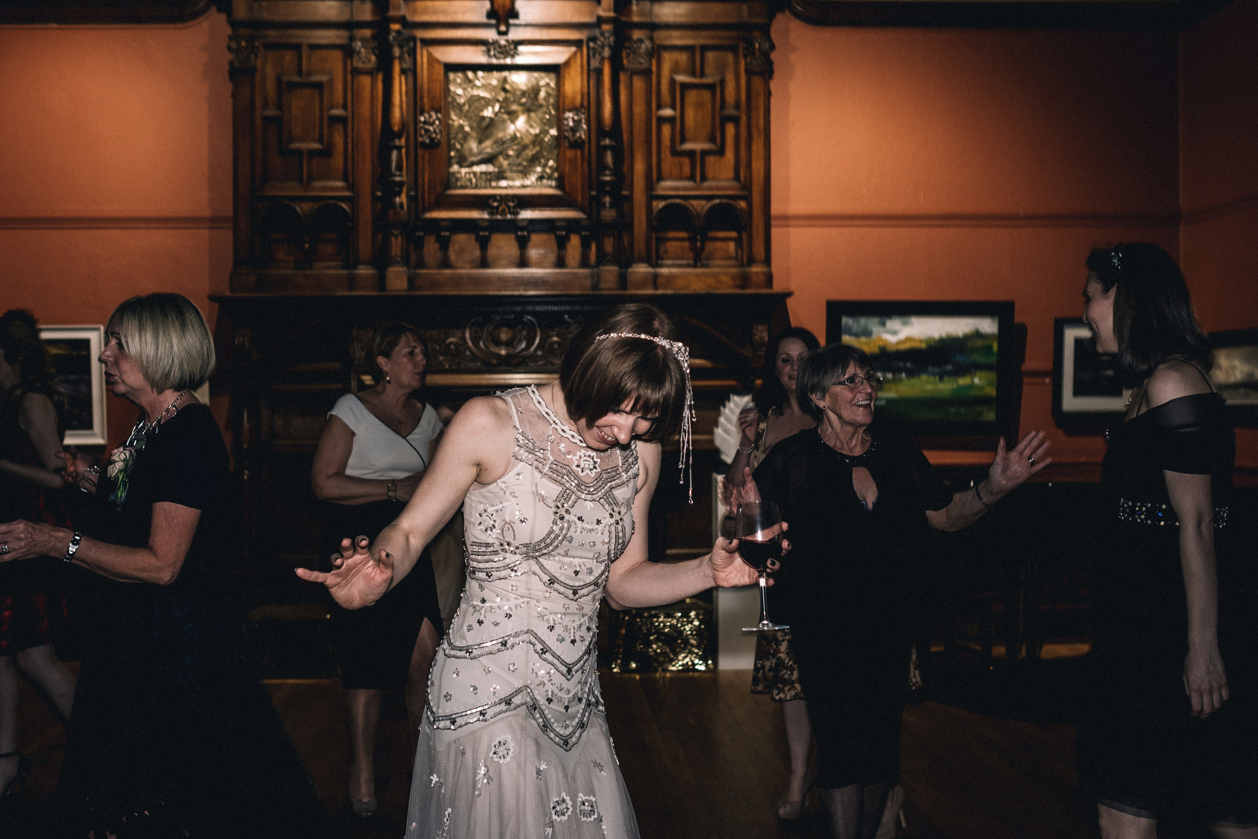 Dancing bride holds red wine glass