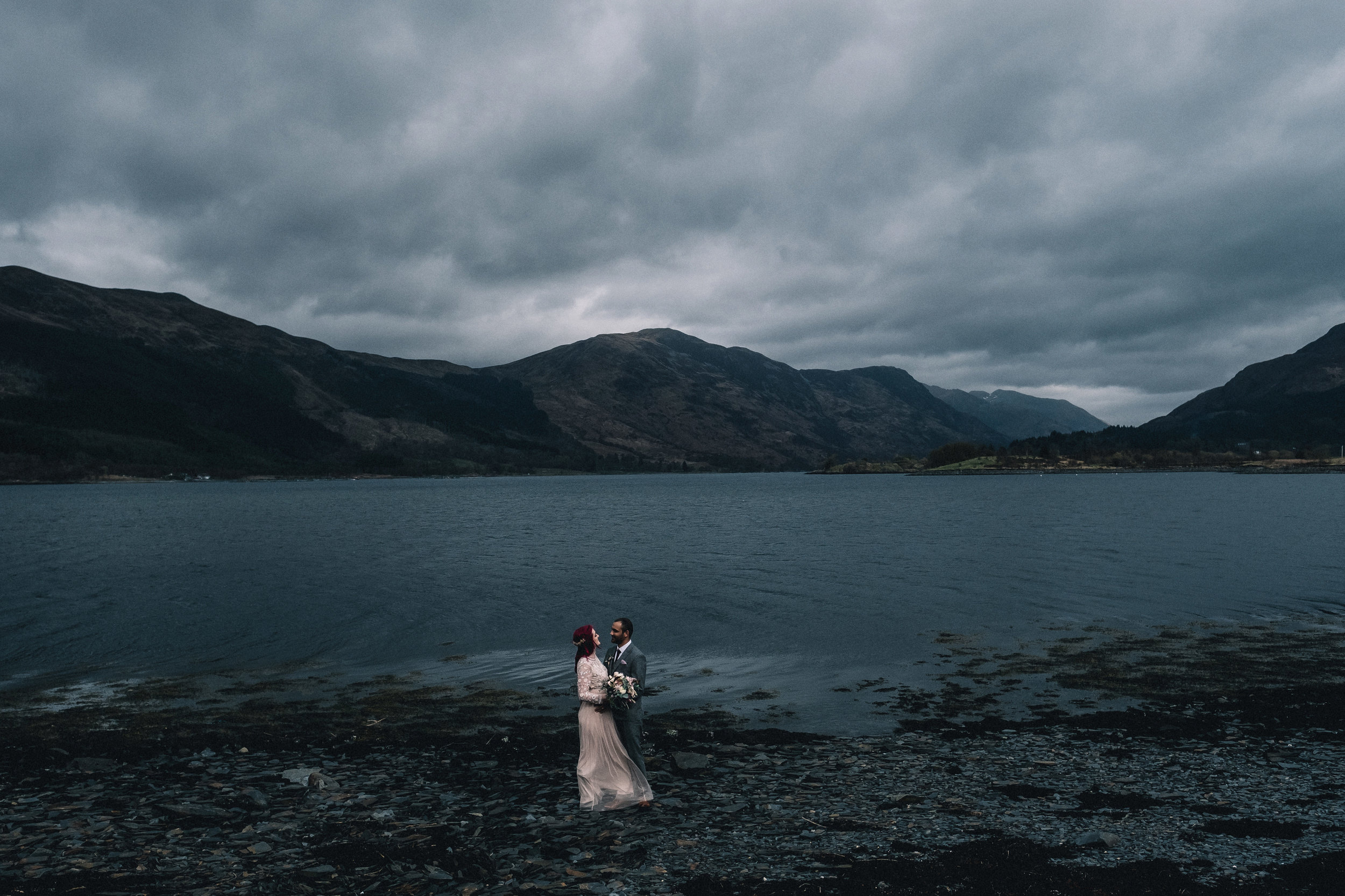 A couple stand on the banks of a loch in Glencoe