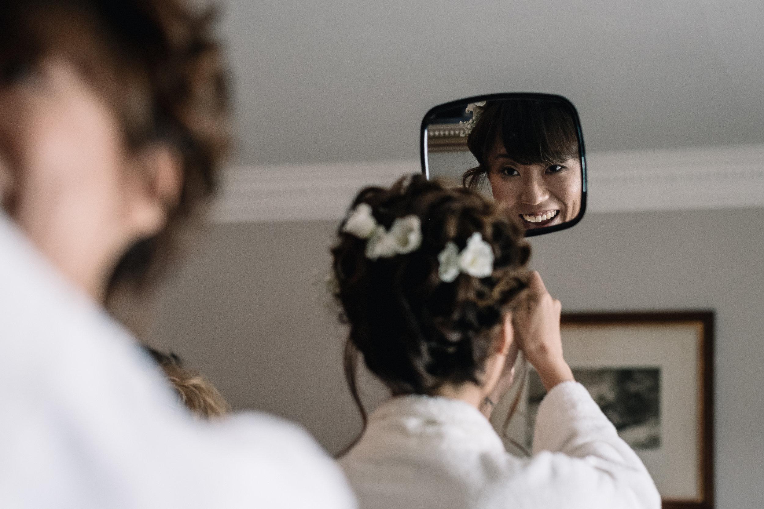 Bride checks hair in hand held mirror