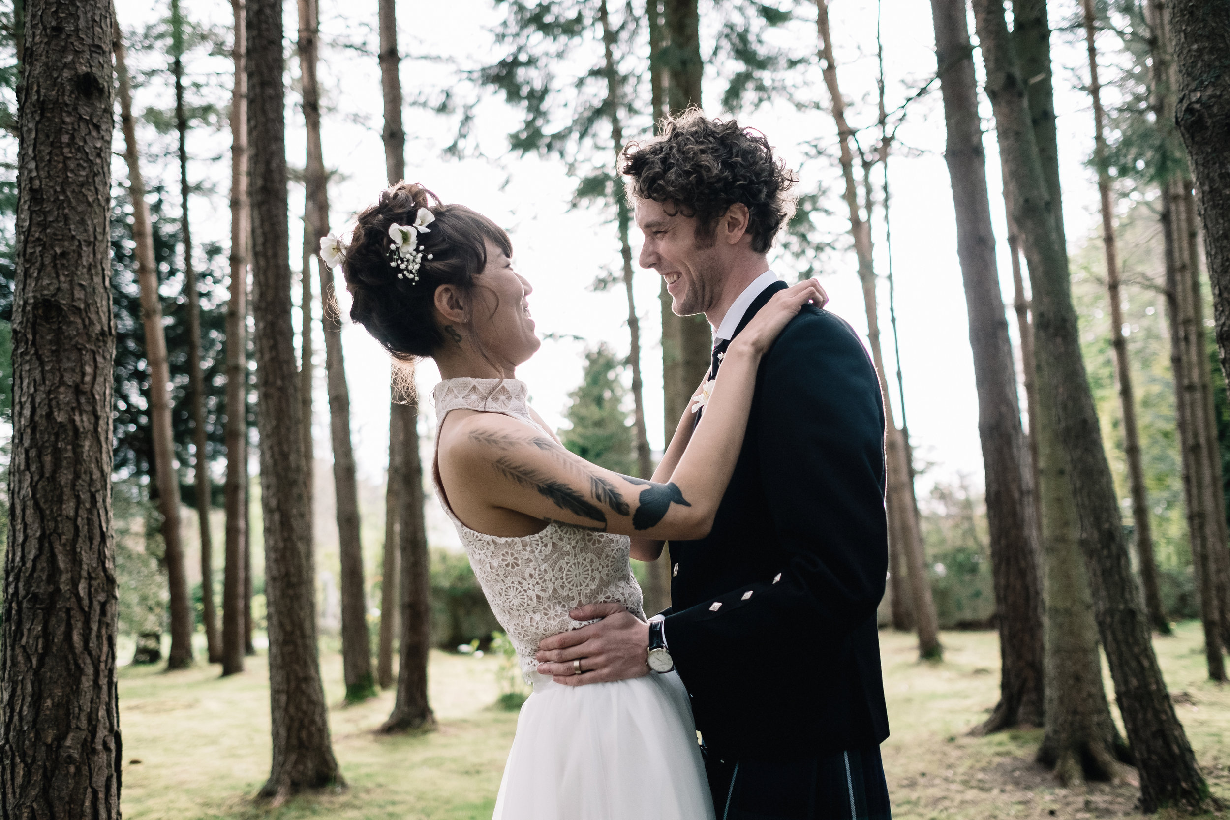 Bride and groom embrace in forrest