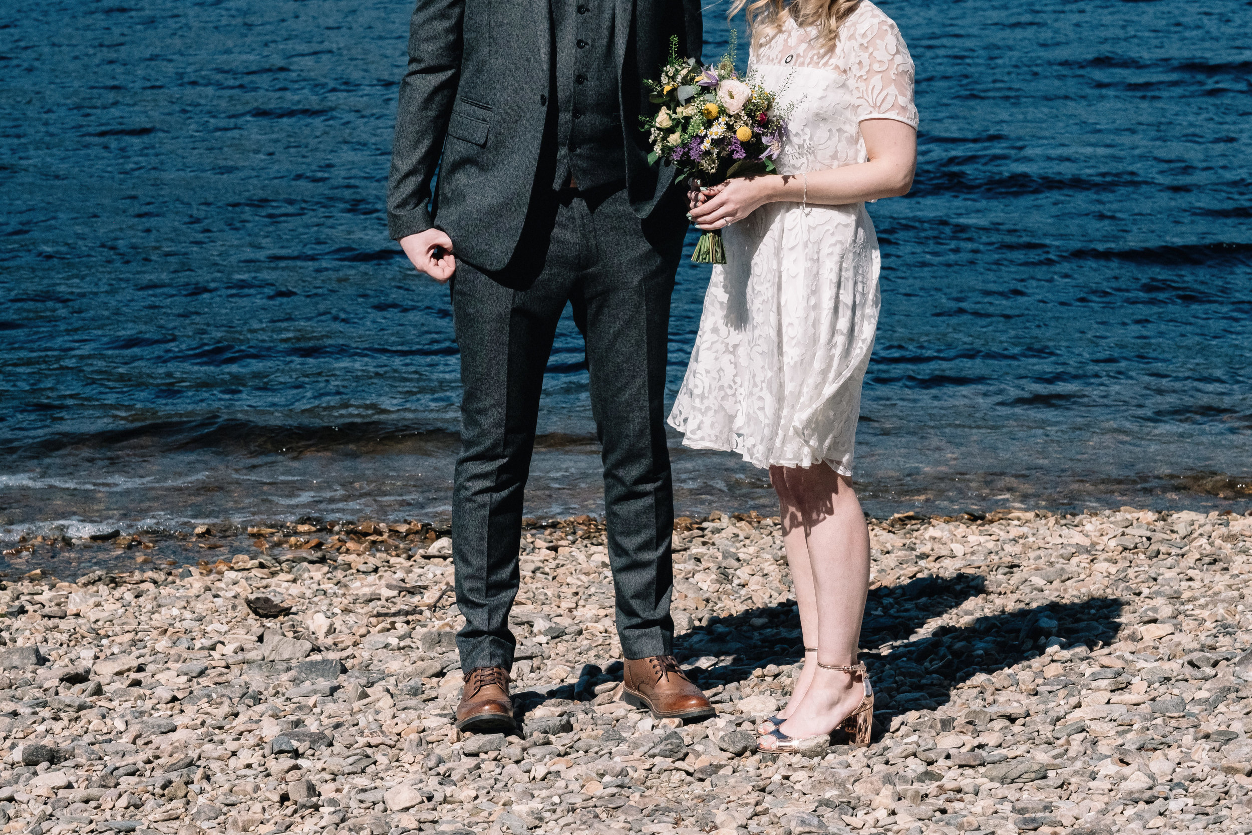 bride and groom standing on pebbled beach