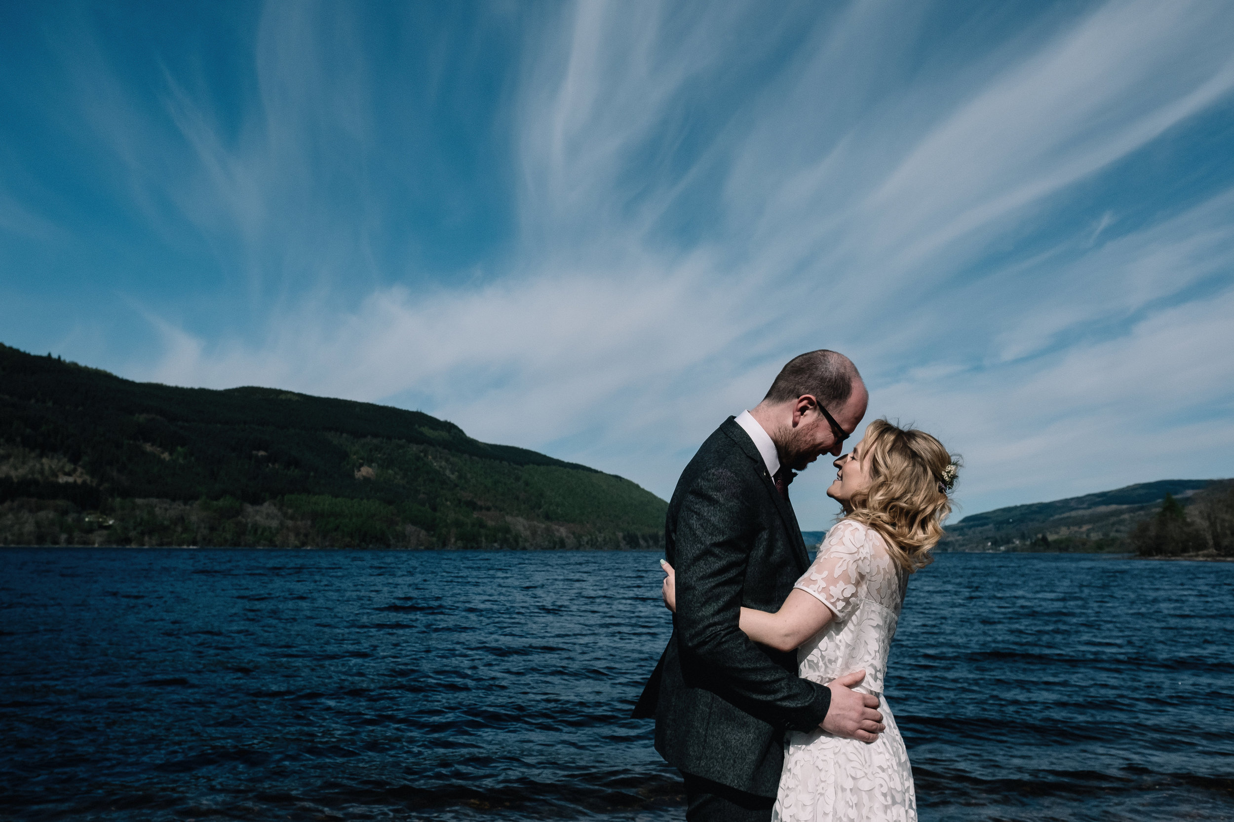 bride and groom standing by loch tay