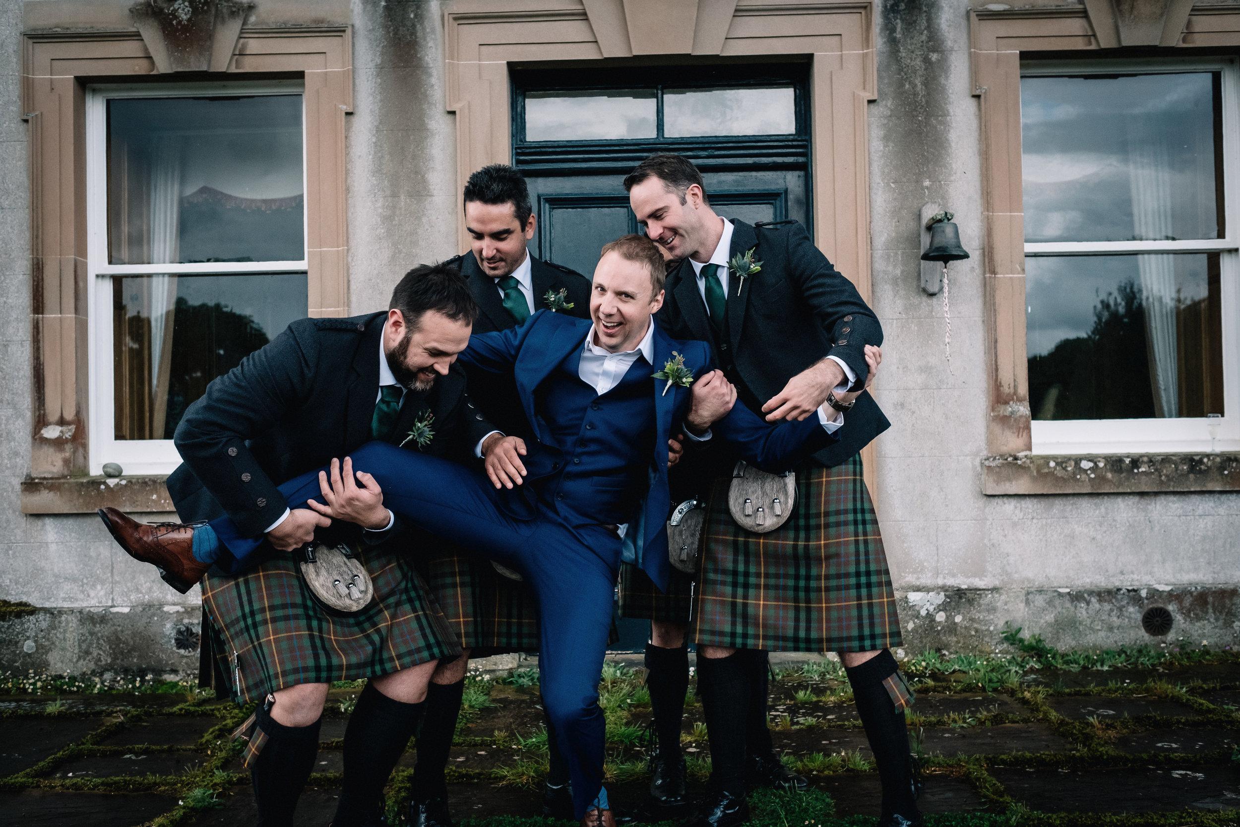 Groom being held by groomsmen
