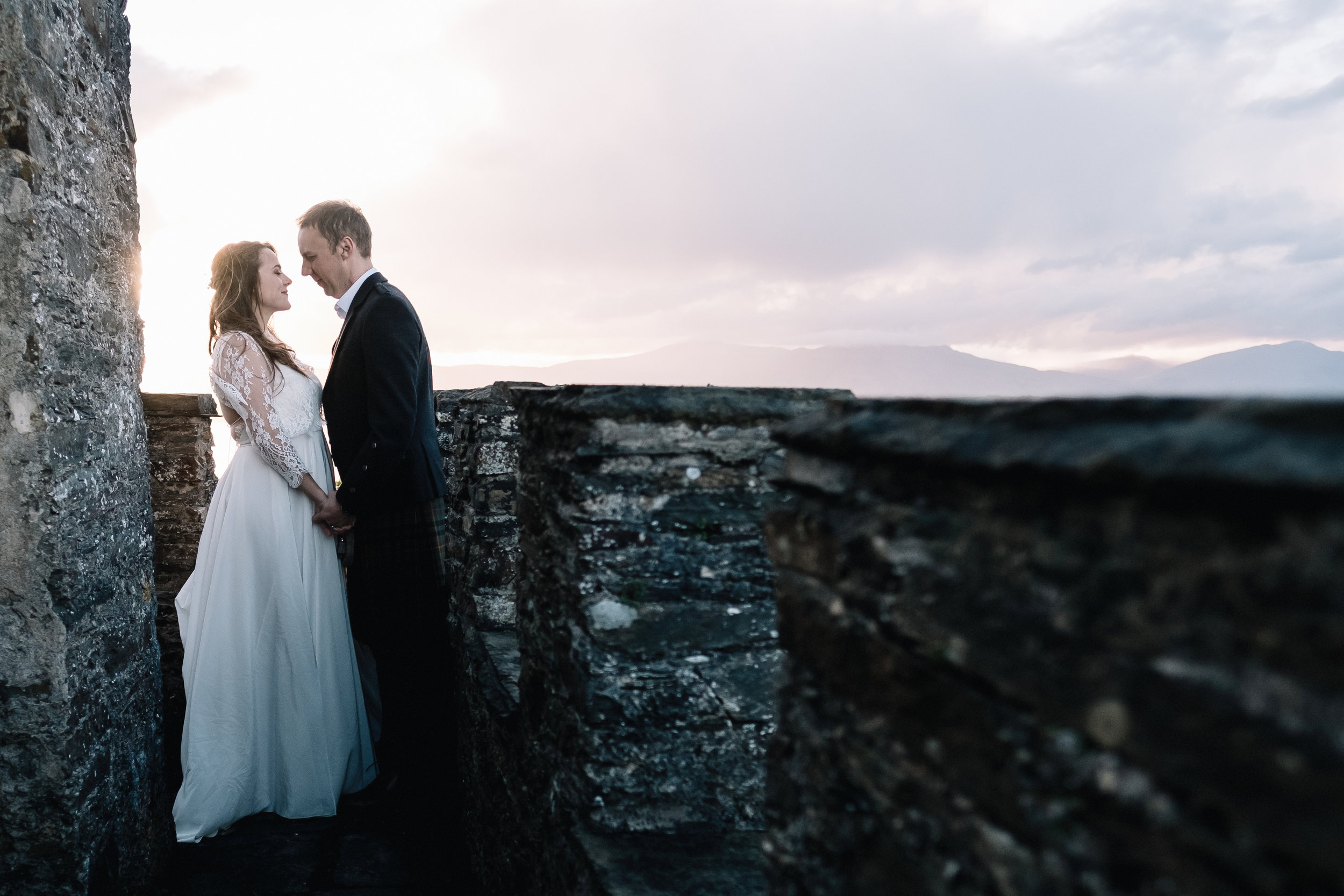 Bride and groom stand on watchtower of Lochnell Castle