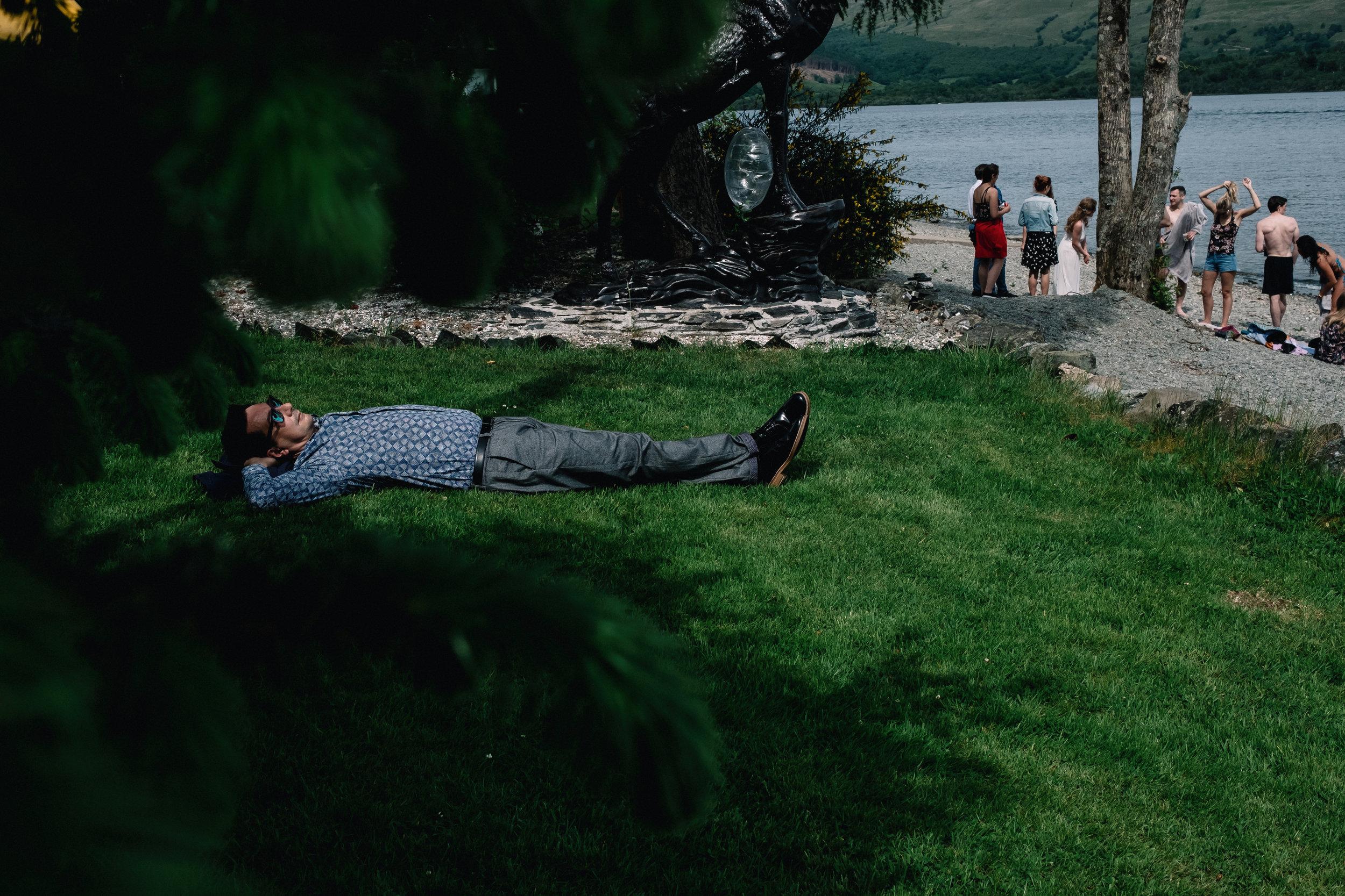 Wedding guest sleeping on grass