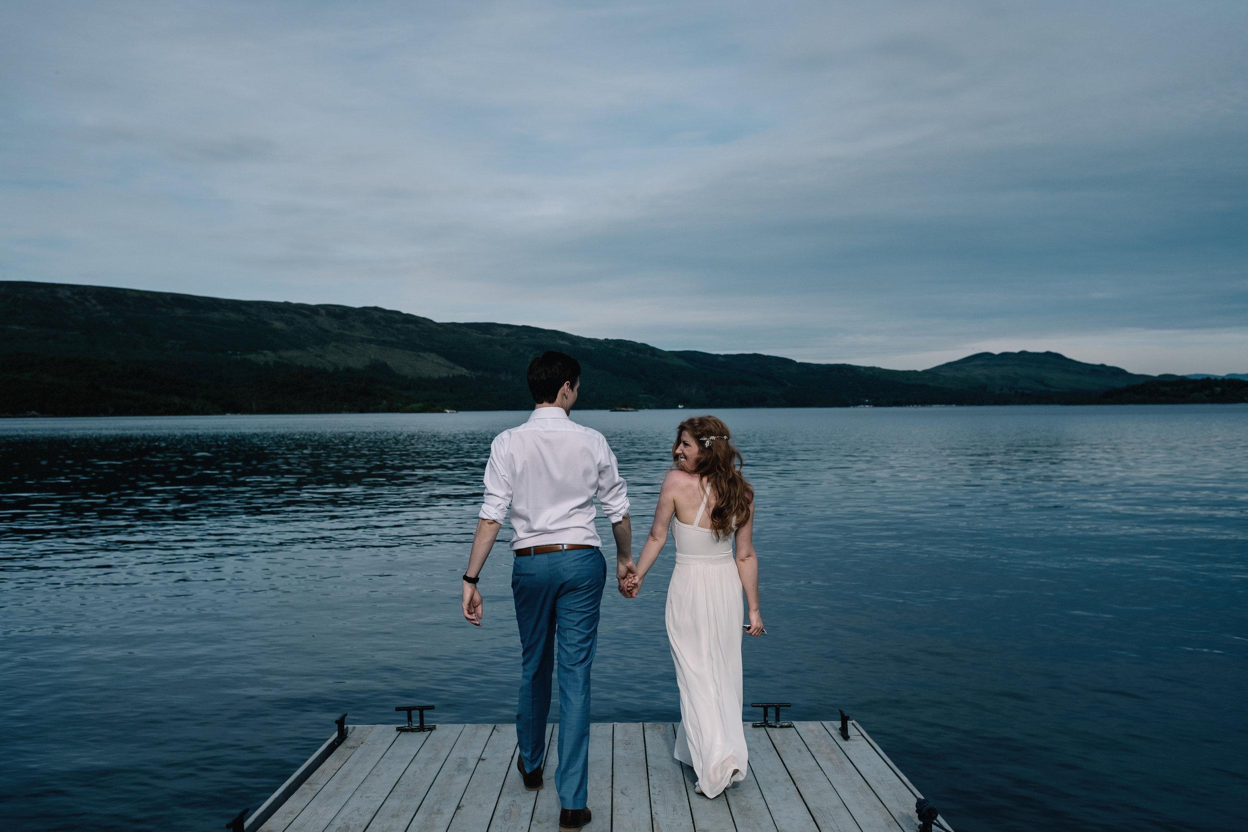 Bride and groom walk on pier