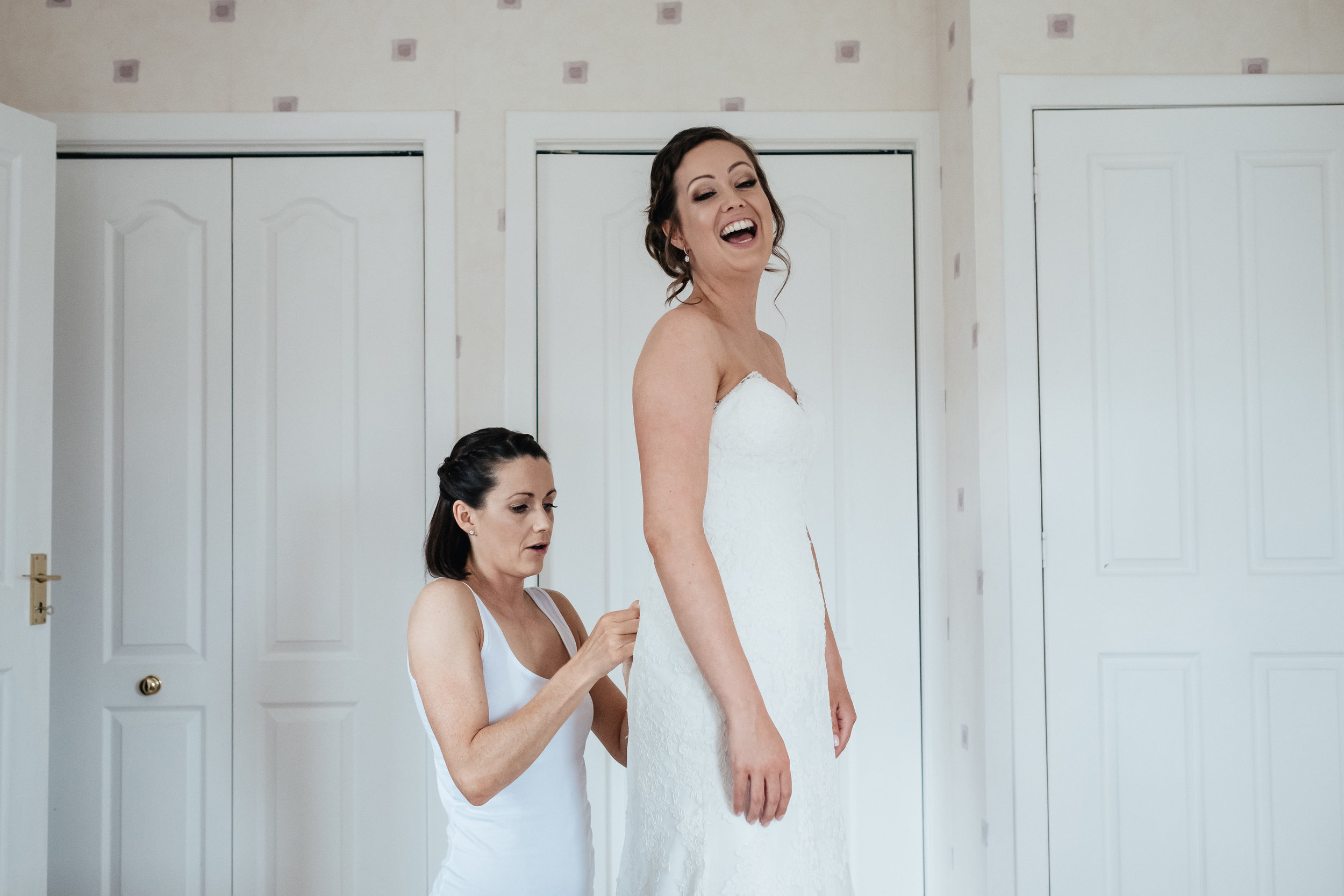 Bride being helped into her dress
