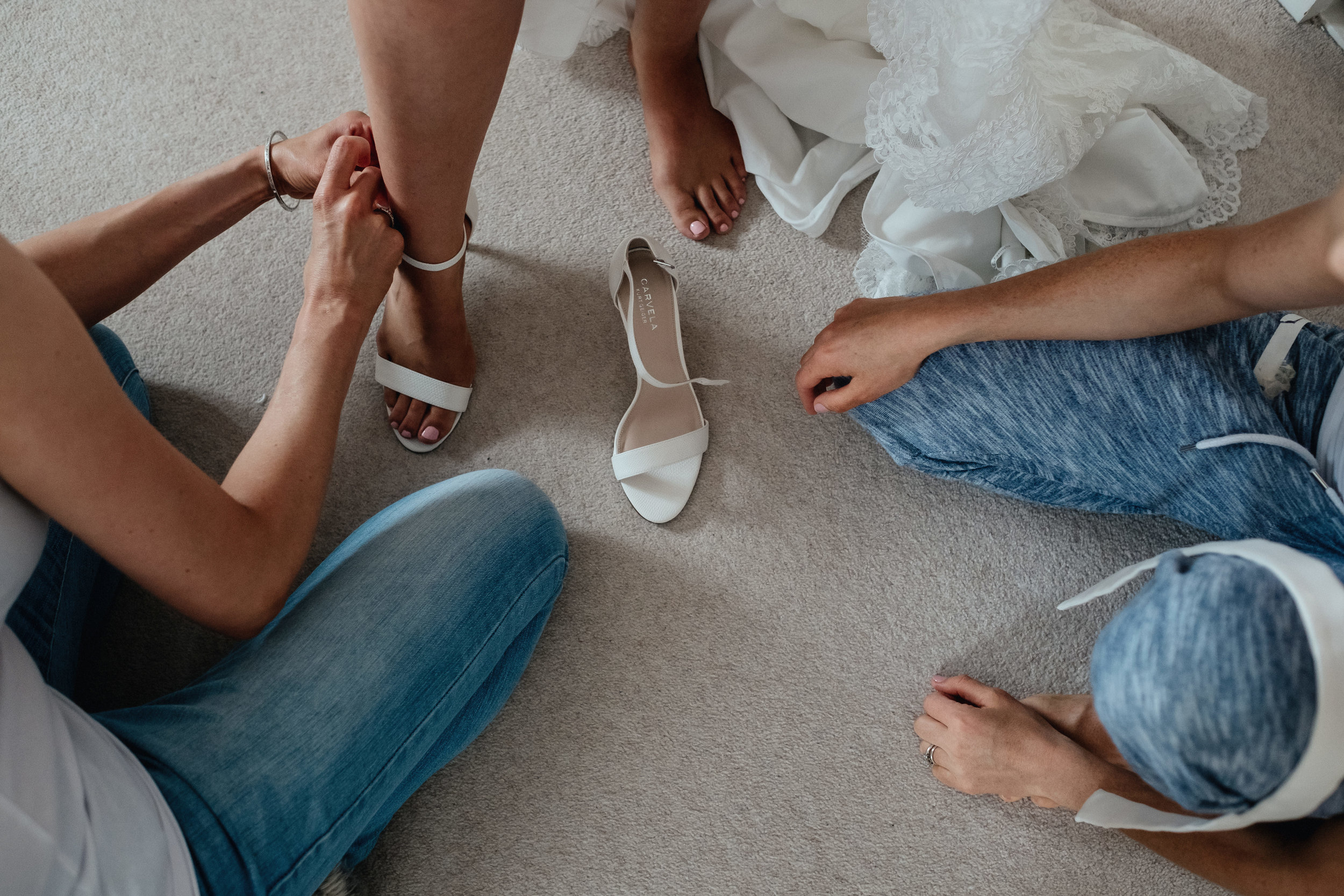 Bride being helped on with her shoes