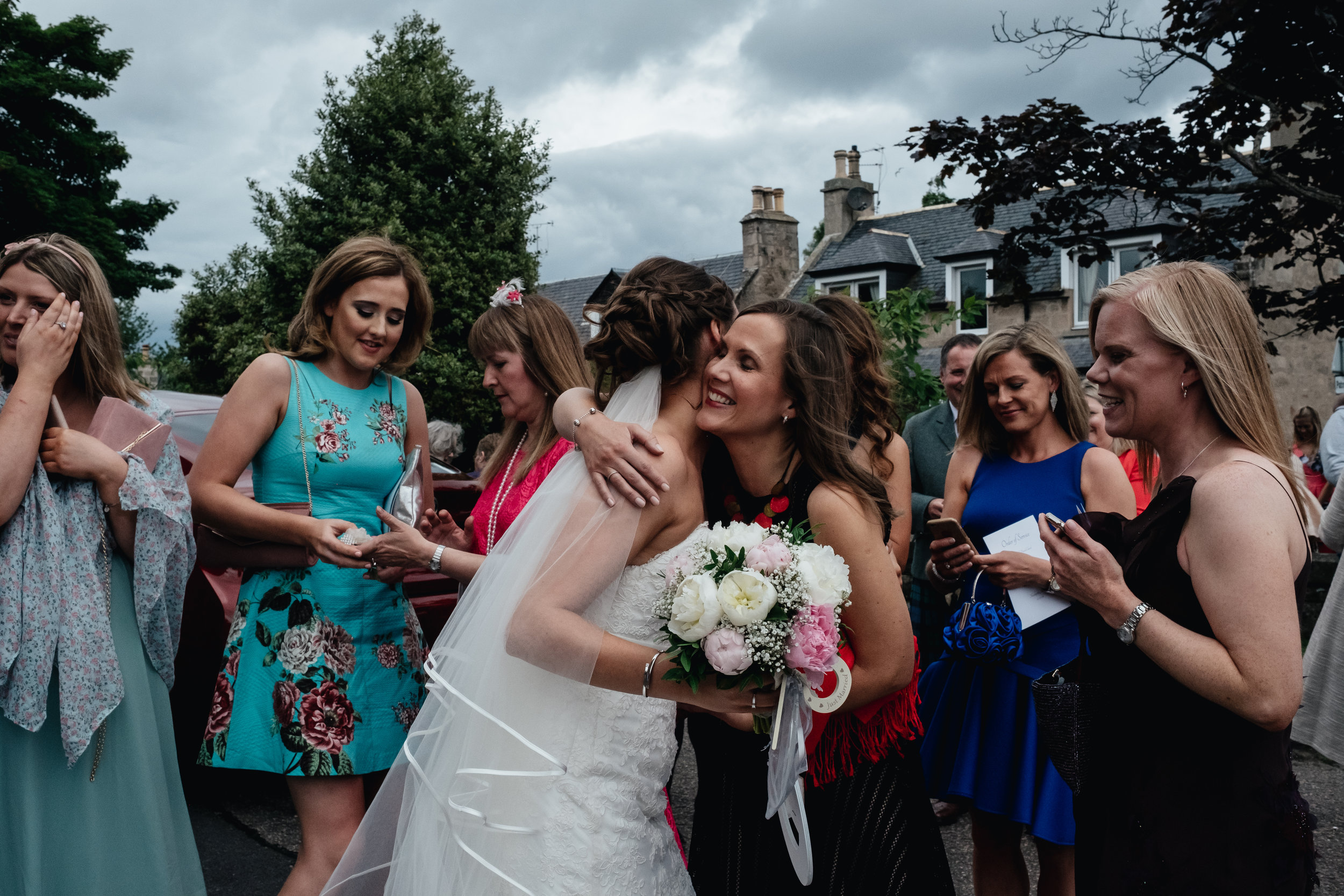 Bride being hugged by friends