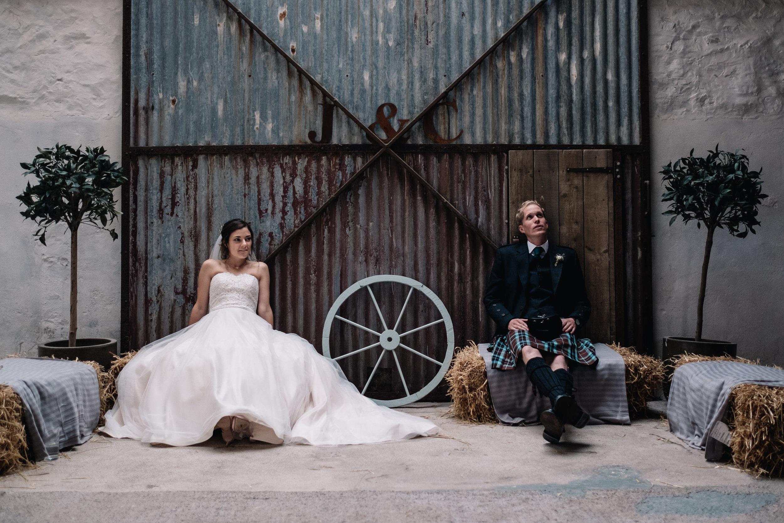 Bride + groom sit against a steel door