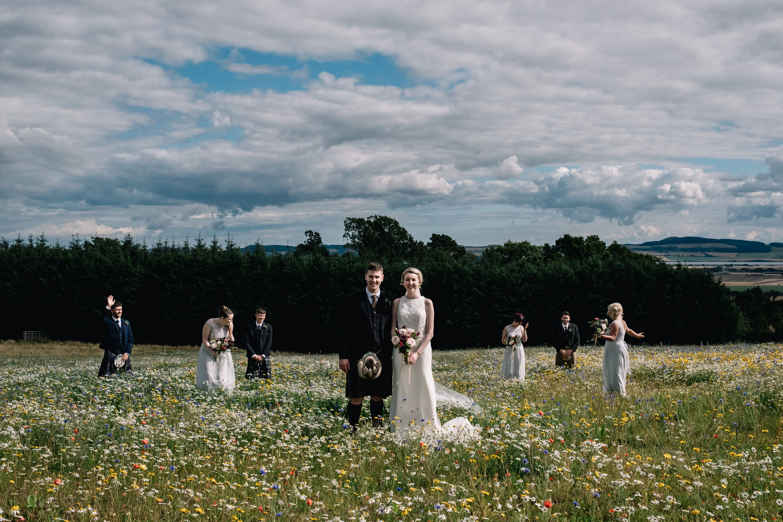 Bridal party stand in field of wild flowers