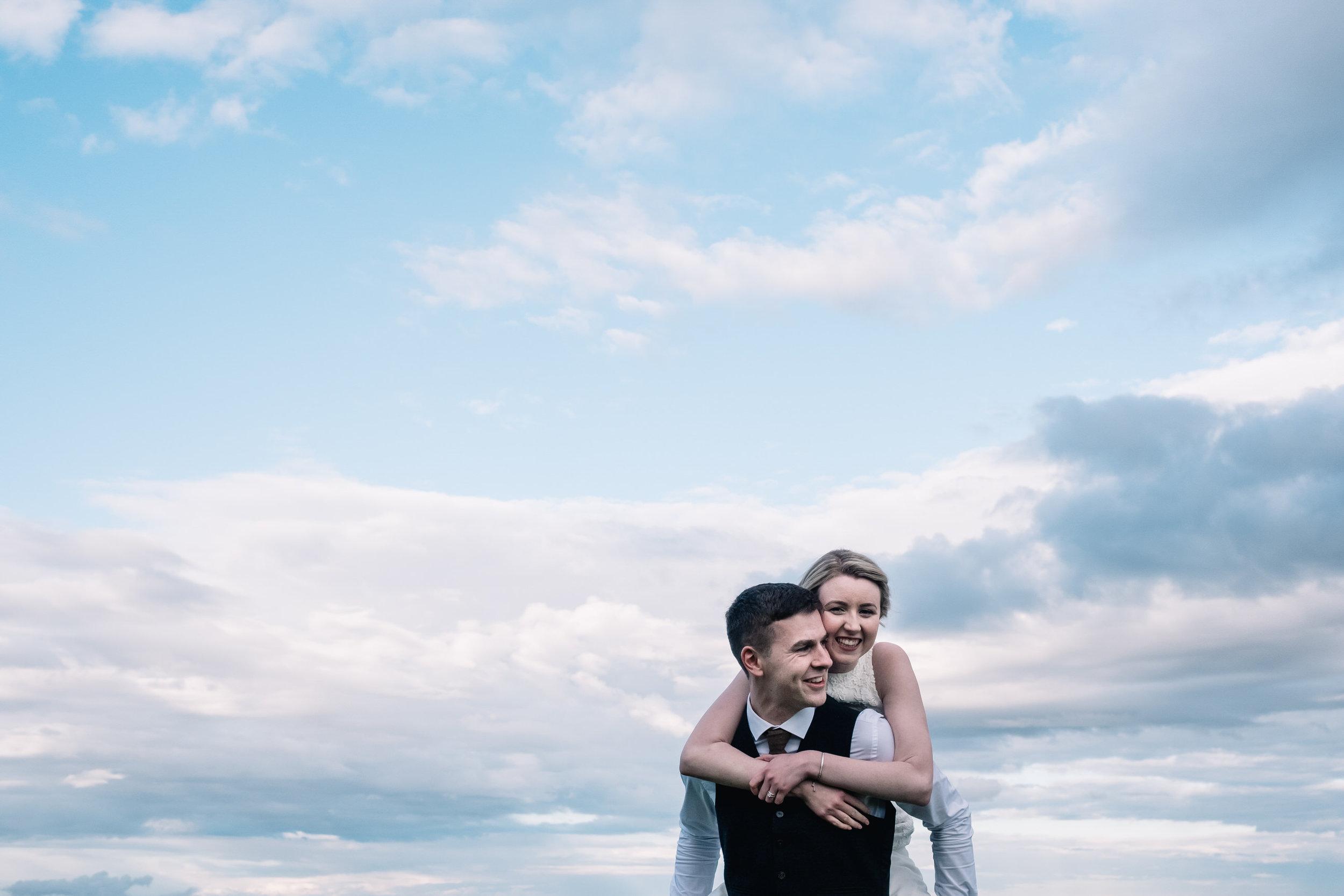 Bride on shoulders of groom.