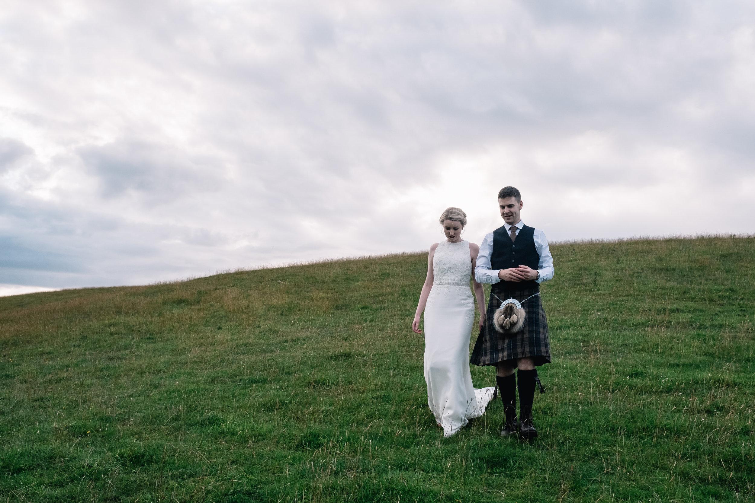 Bride and groom descend hillside side by side