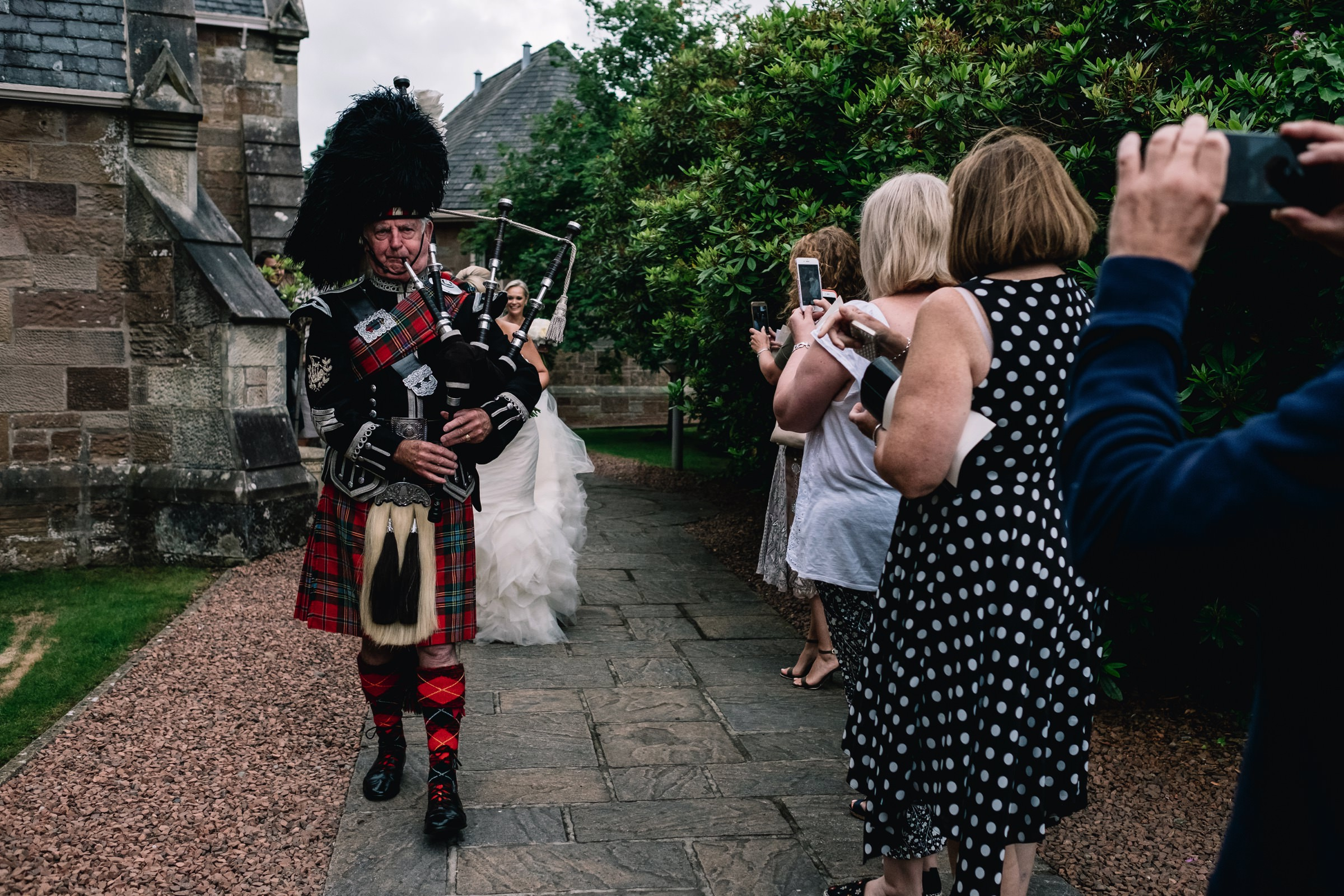 Bride and groom being piped from church