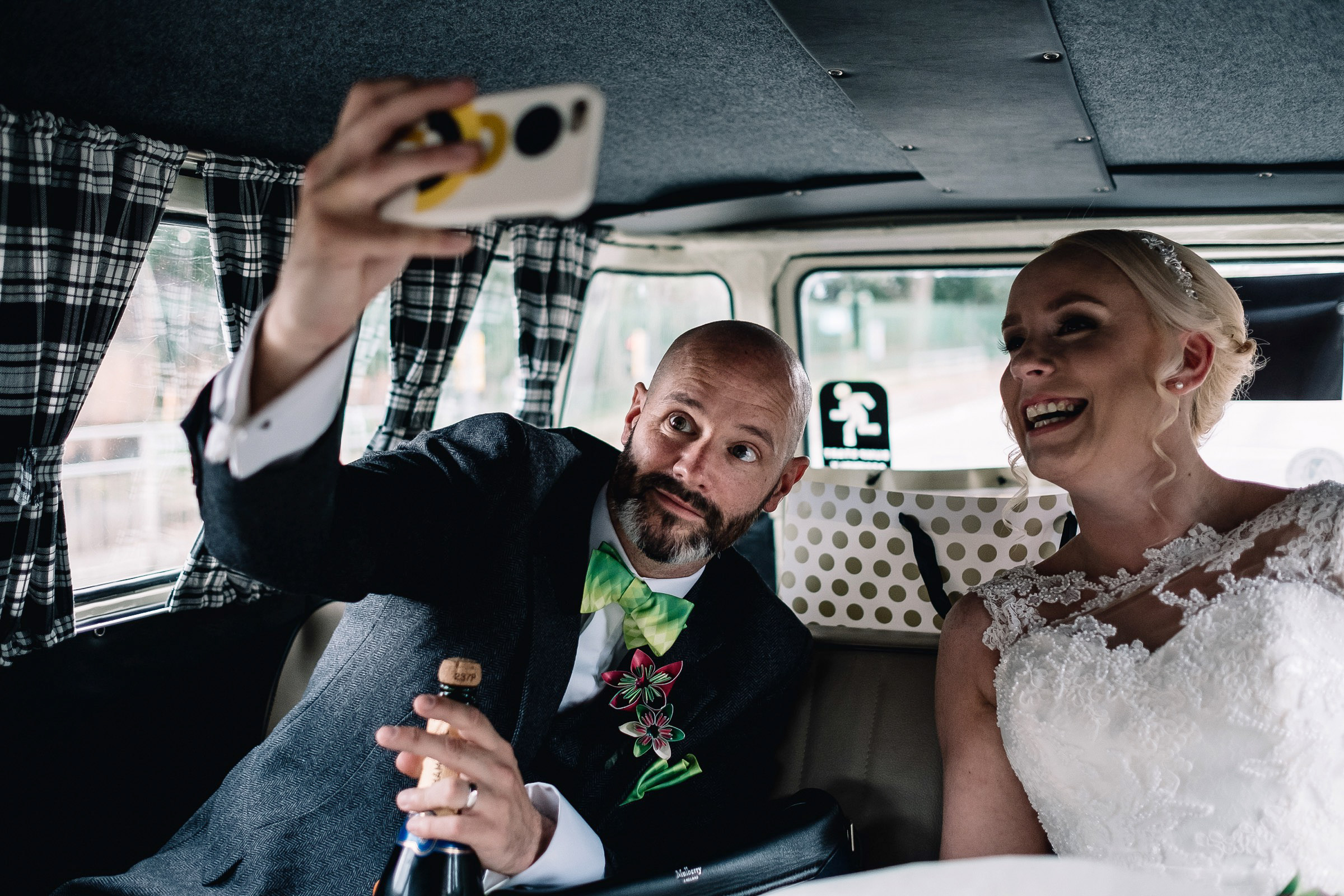 Bride and groom taking selfie in camper van