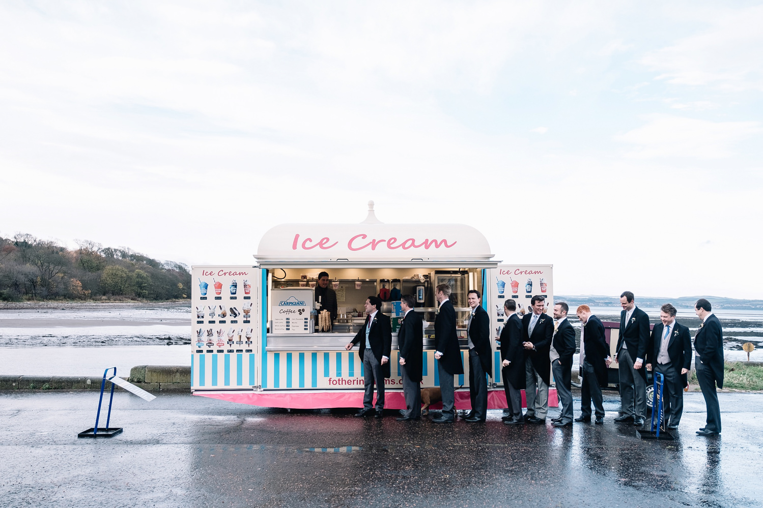 groomsmen all wearing morning suits lining up for ice cream