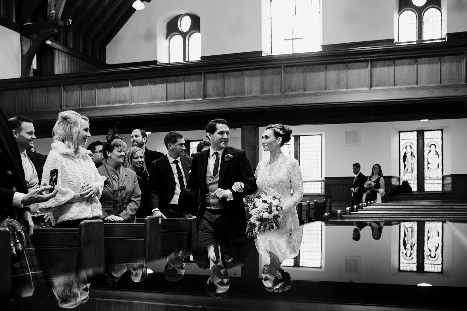 reflection of bride and groom on piano after they've signed the register