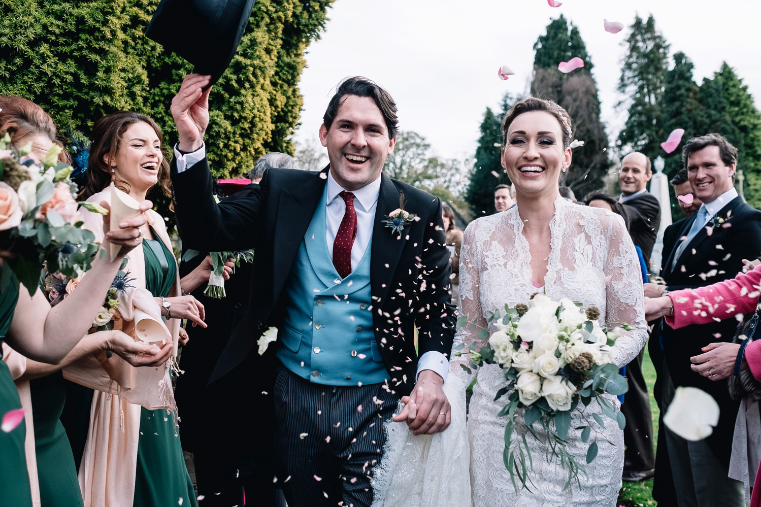 Groom takes off top hat during confetti walk.