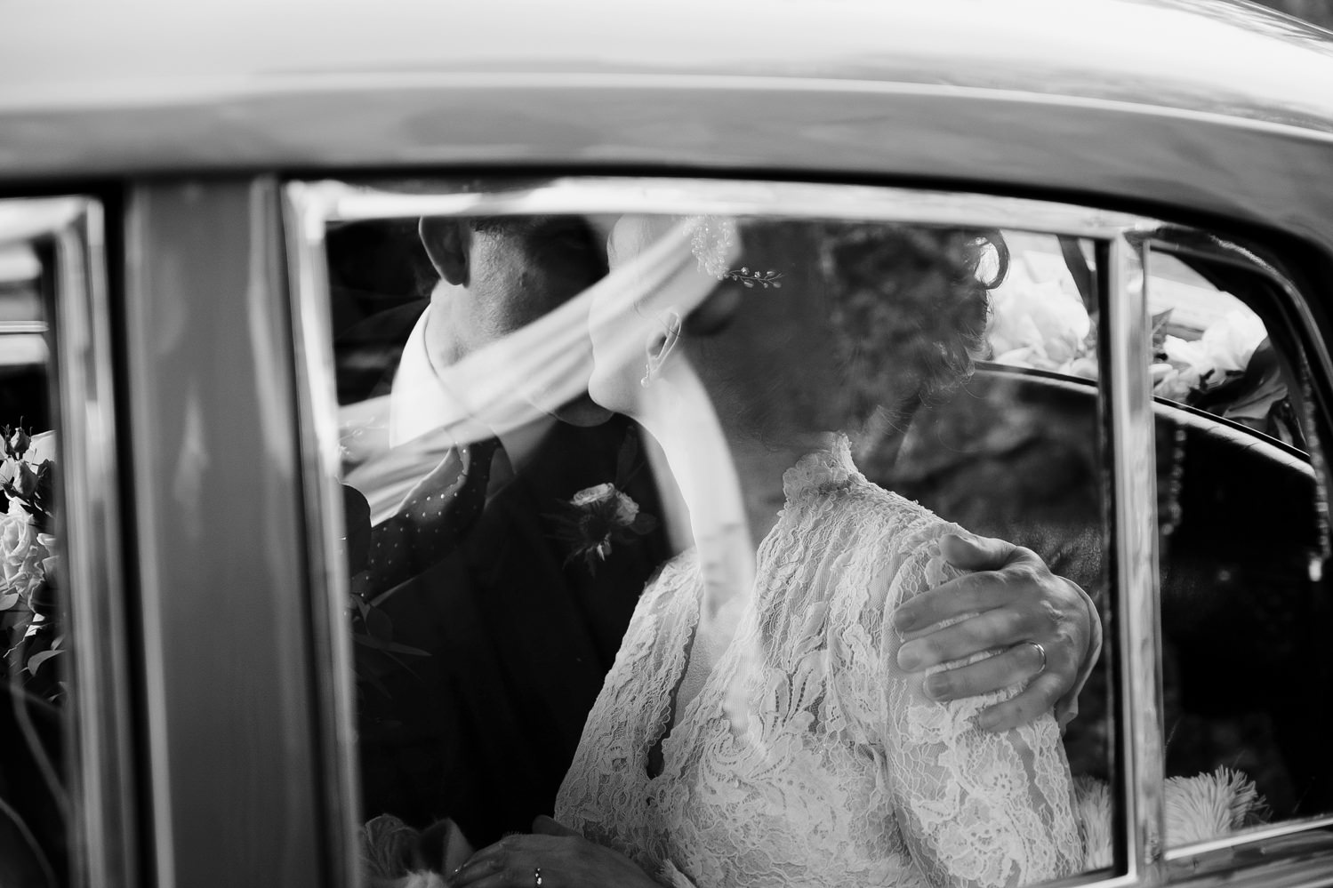 Bride and groom kiss in back seat of classic Bentley