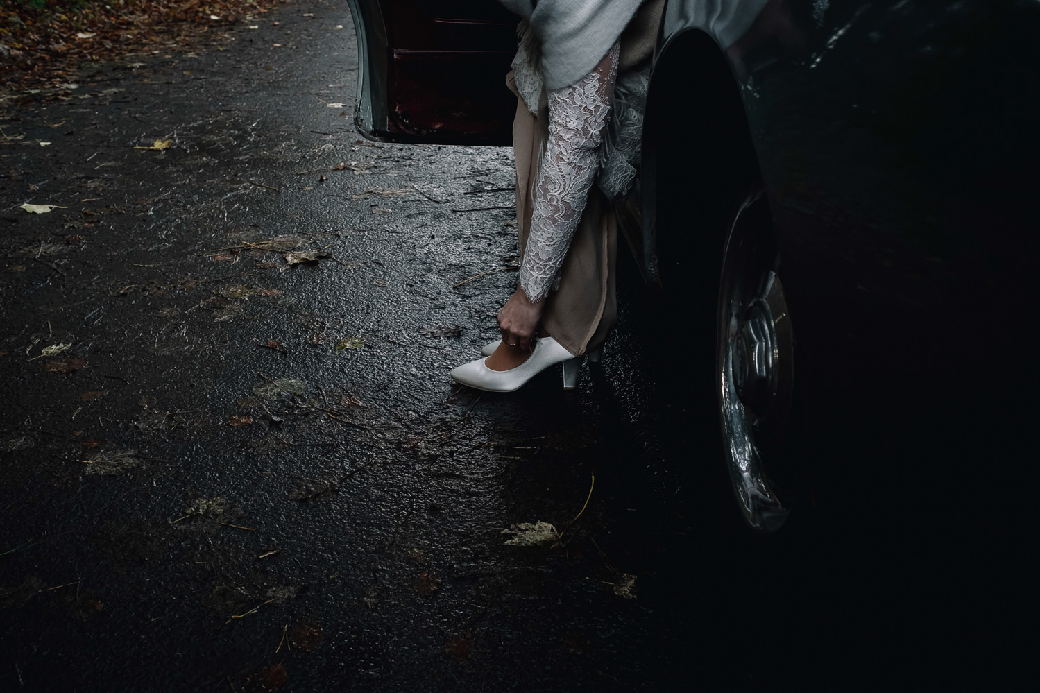 Bride leans out of Bentley to change her footwear on a winter's day
