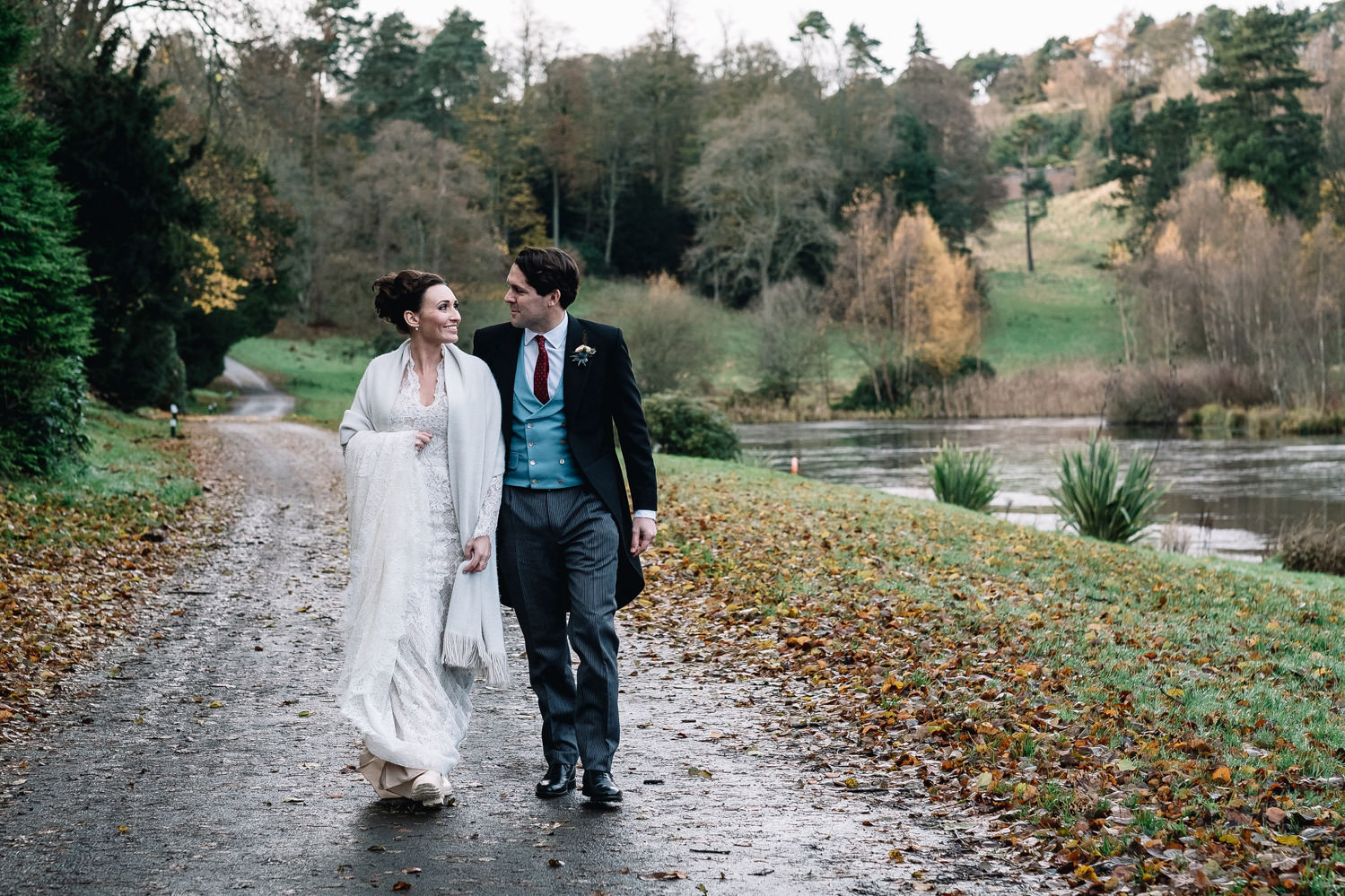 couple walking next to loch by the Dundas Castle Boathouse on their winter wedding day