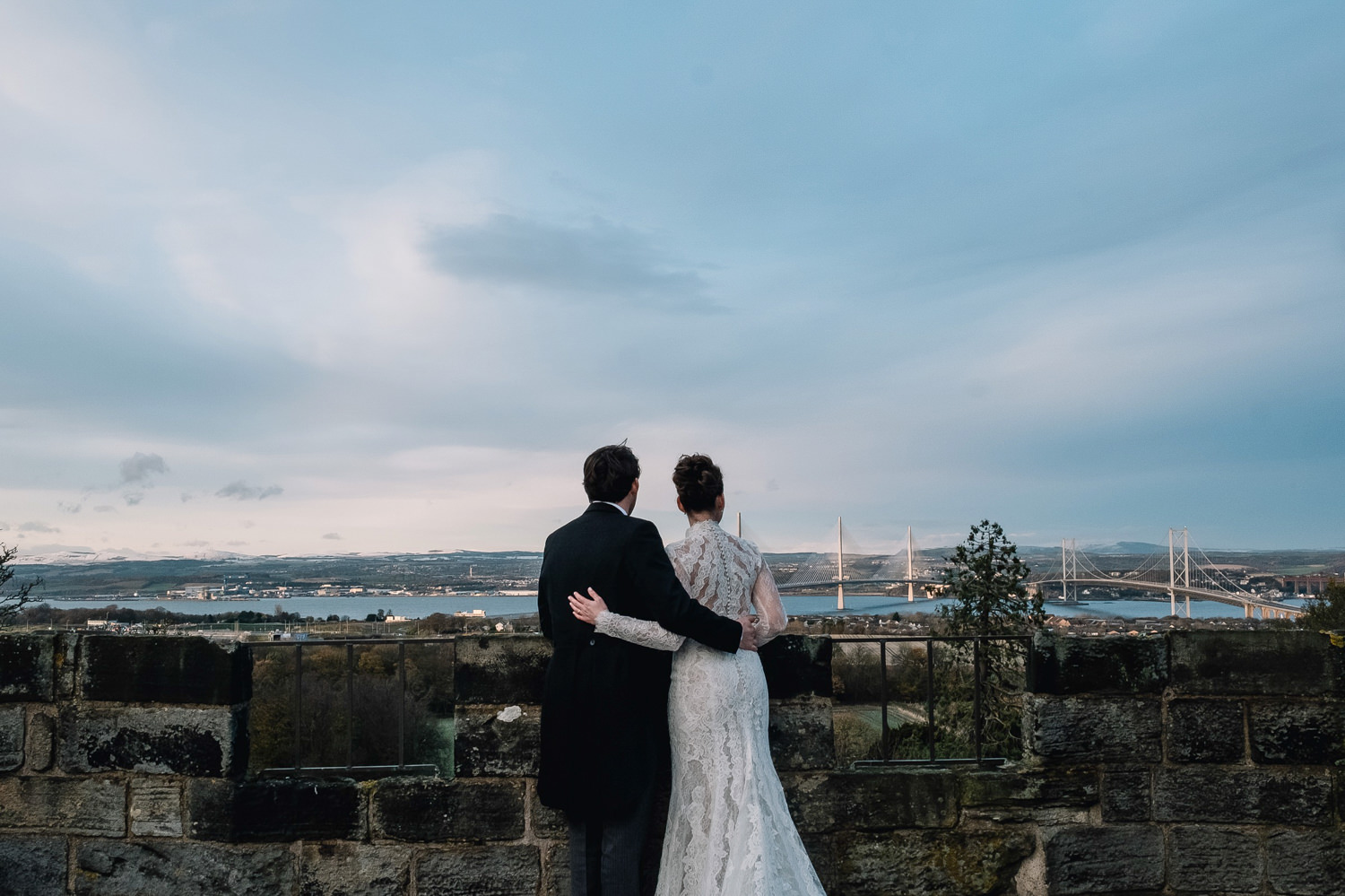 couple stand looking at view of edinburgh on a winter wedding day