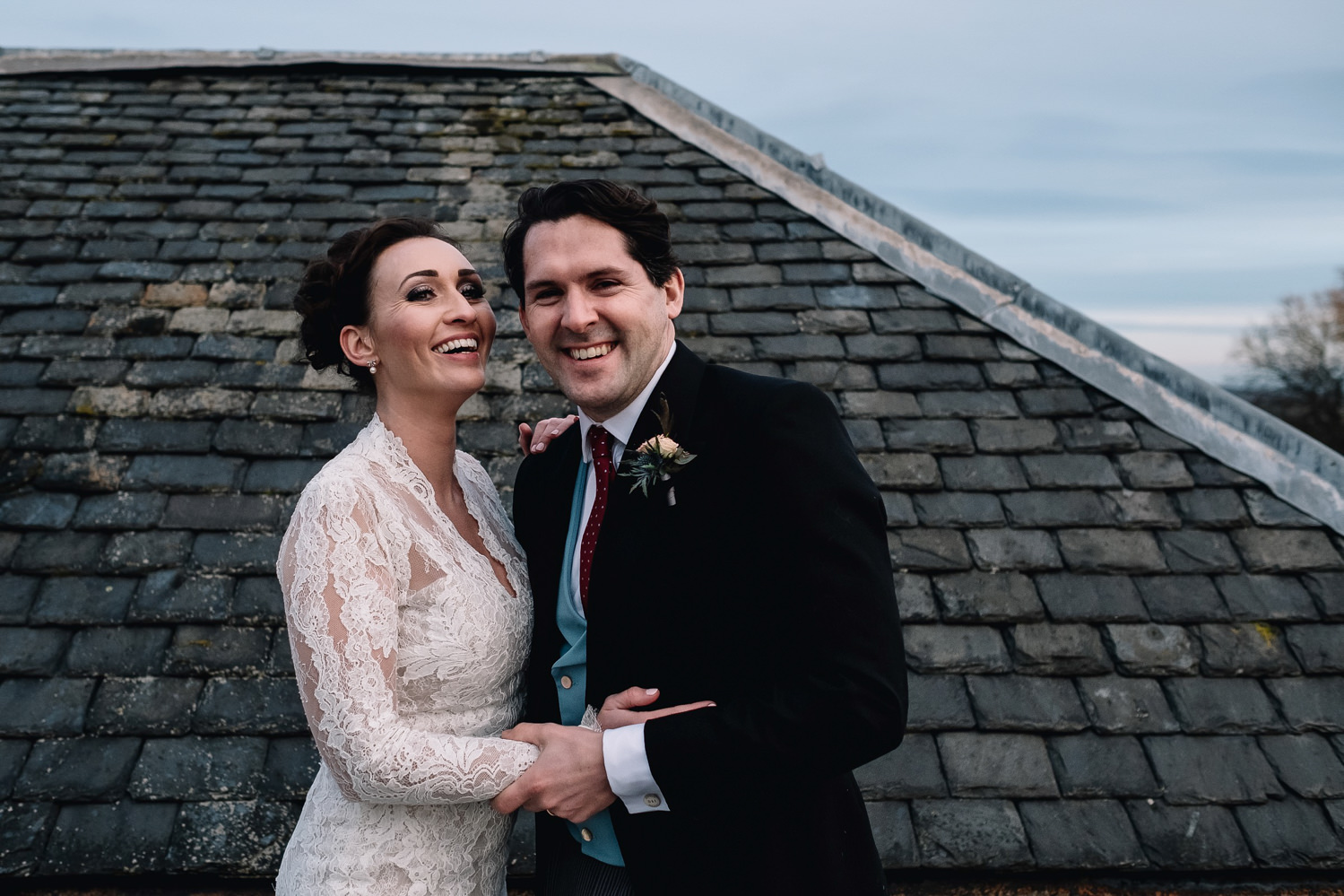 laughing bride and groom on rooftop of Dundas Castle's keep