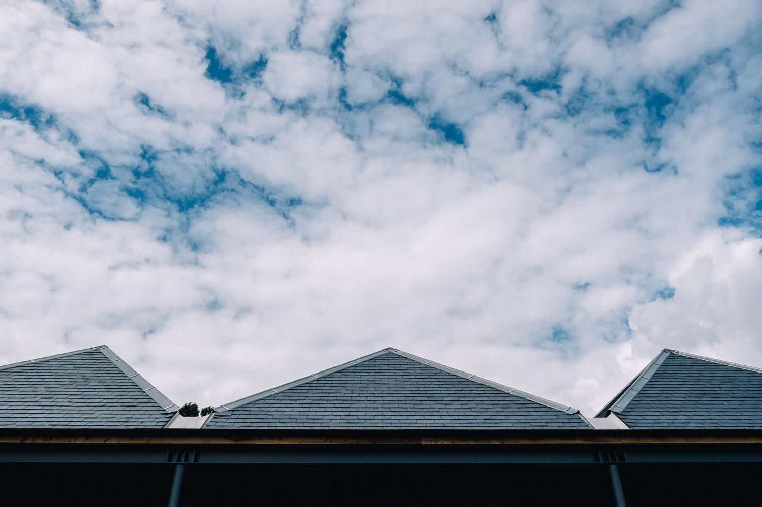 Three raised triangular turrets of the Guardswell Farm barn are in focus.