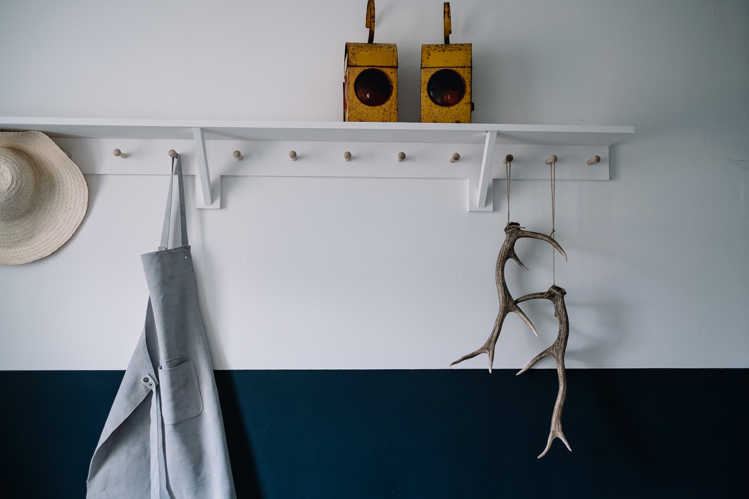 Stag antlers hang alongside an apron on the coat hook in the boot room.