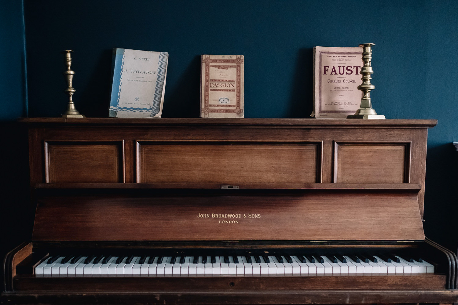 Piano in the Guardswell cottage with sheet music on top stands out against the muted blue wall.