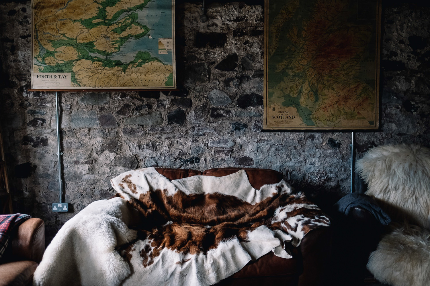 Double seater chair with a cow hide throw in the Cosy Room is focus of this photo.