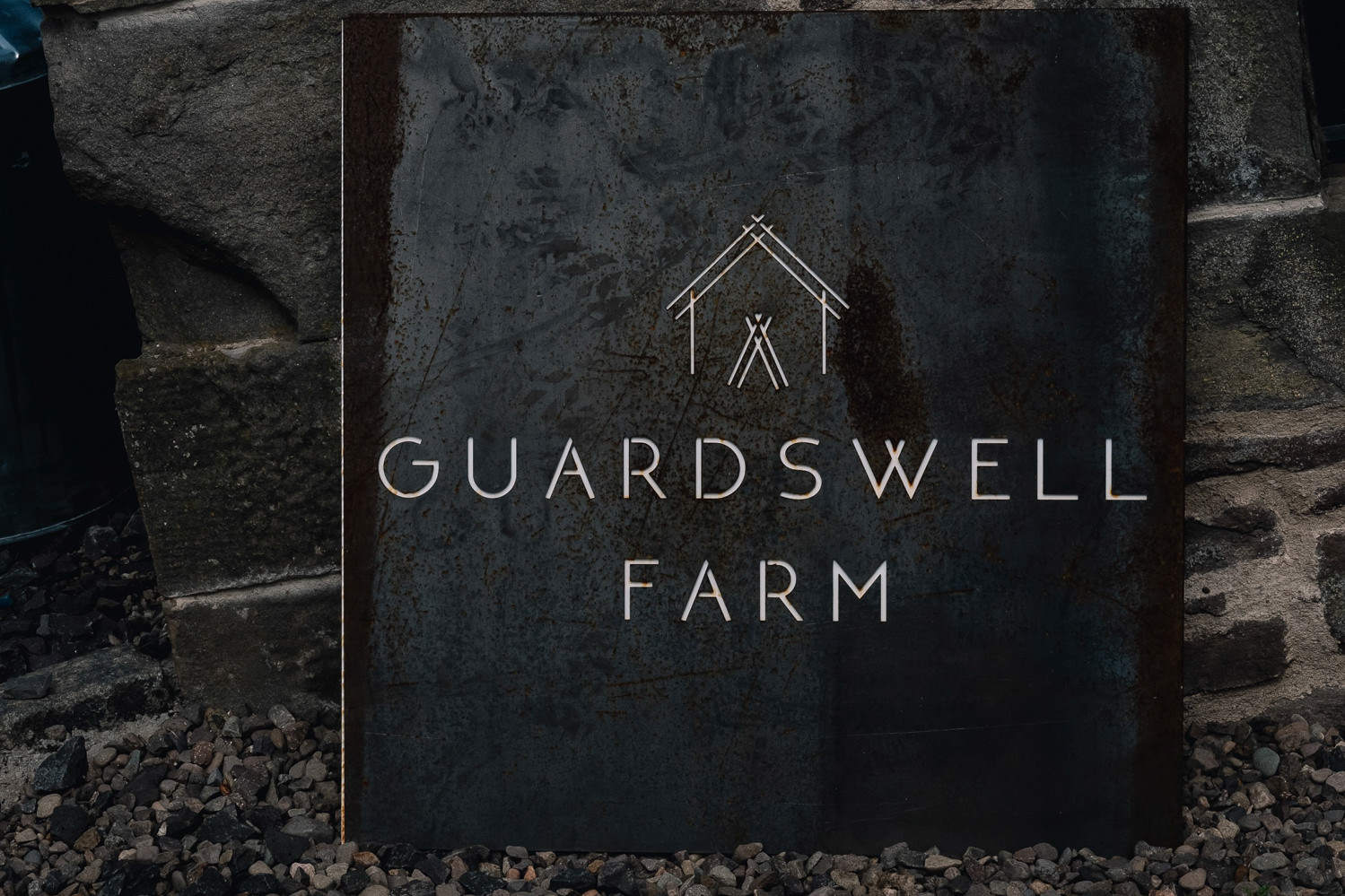 Slate with name and branding logo of Guardswell sits on the ground.