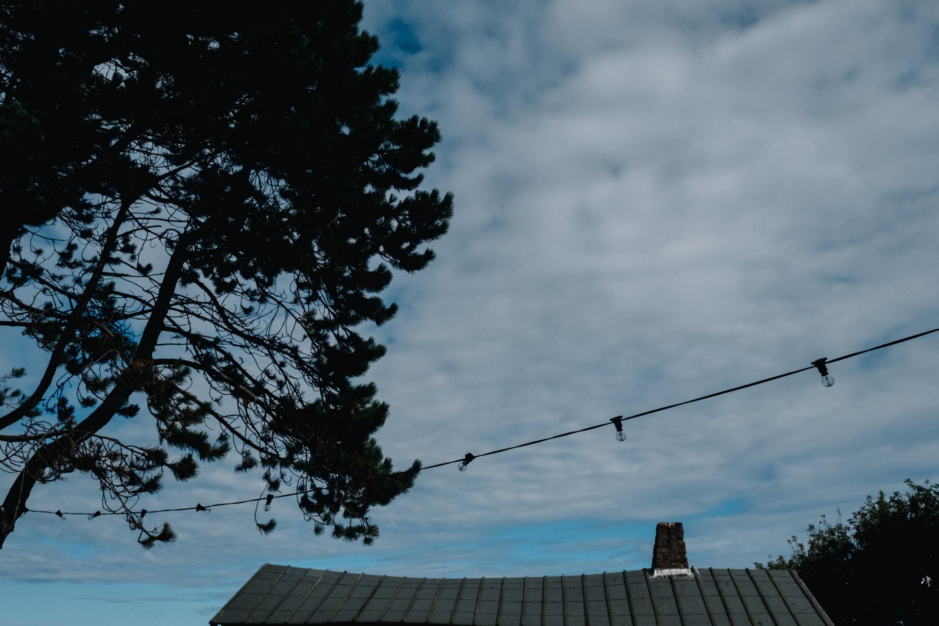 Blue skies over the log cabin at Dunbar and festoon lighting.
