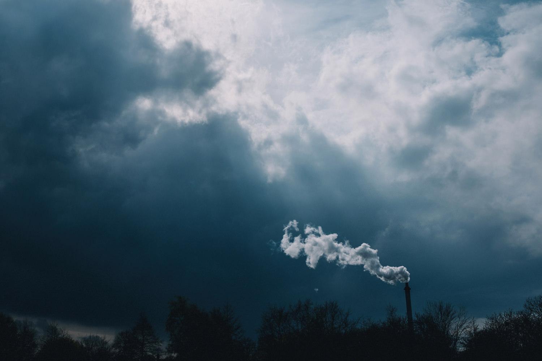 Stormy blue skies contrast against industrial smoke.