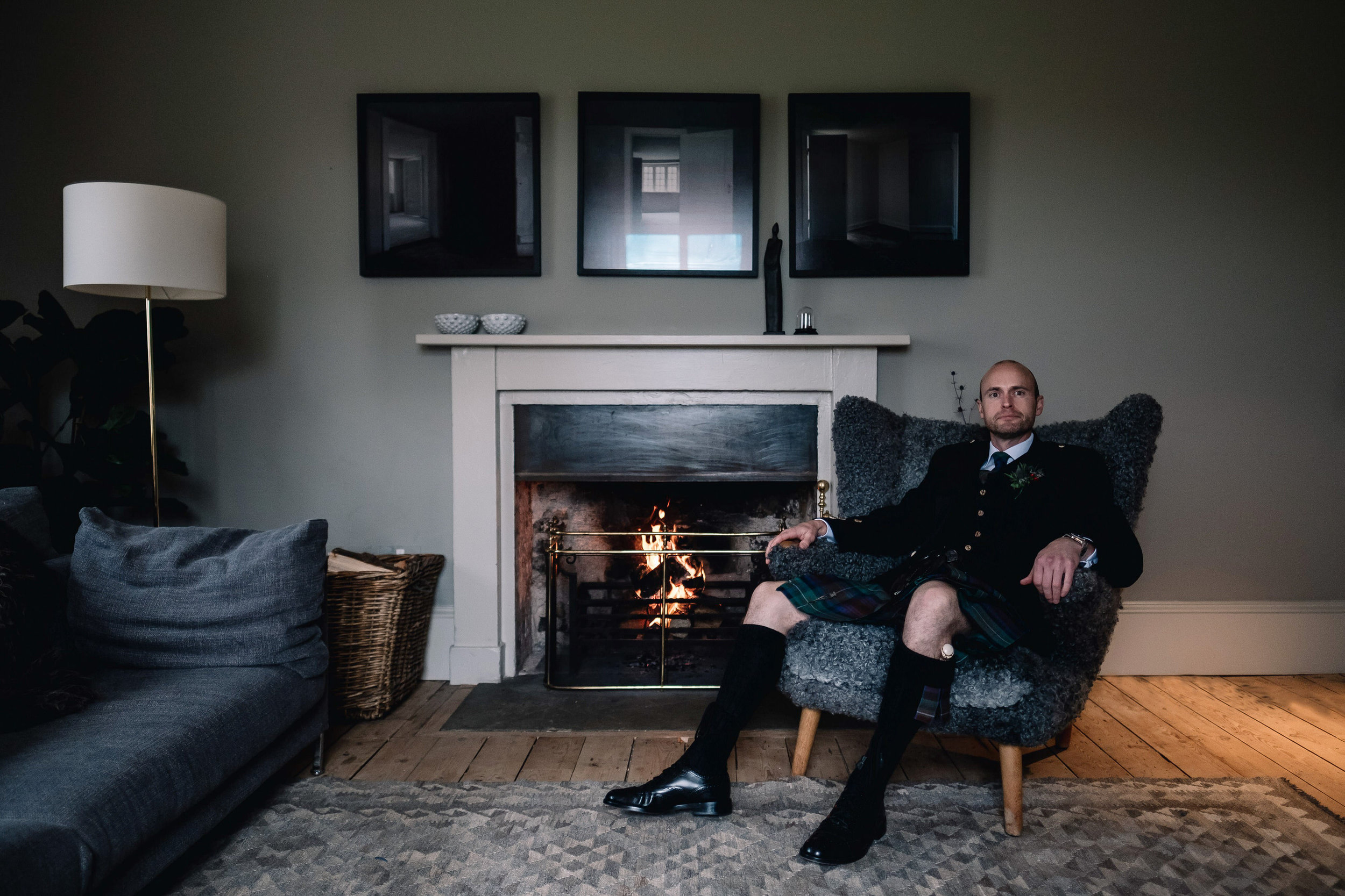 Portriat of groom sitting by log fire.