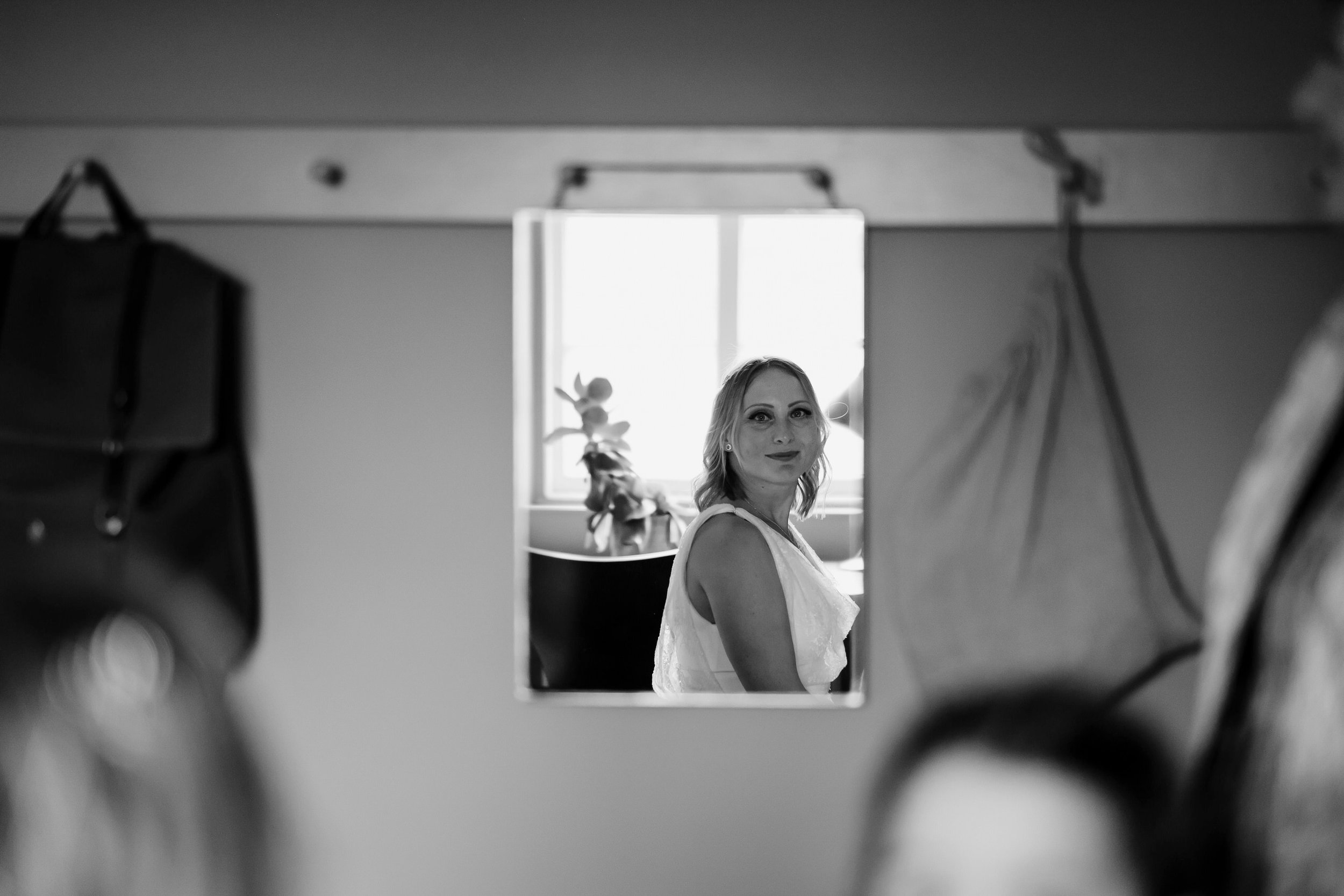 Bride looks at herself in the mirror.