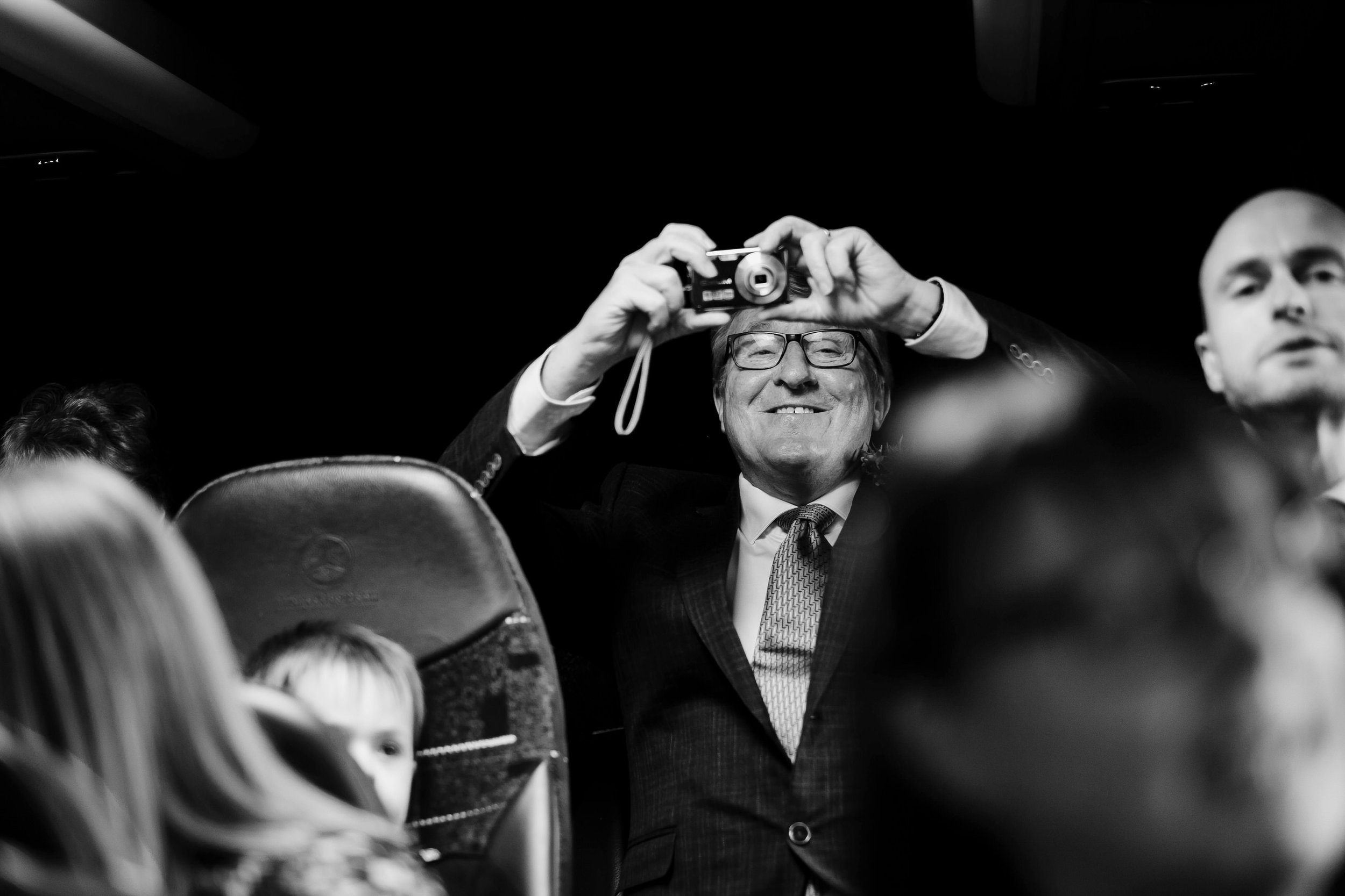 Father of the bride takes a photograph of the journey to the courthouse from the backseat of the bus