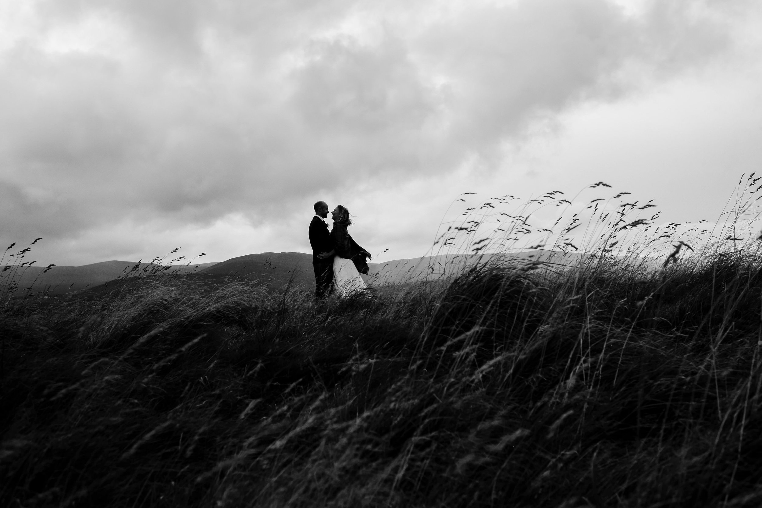 Bride and groom stand in open fields of Kingussie during their small intimate Scottish wedding