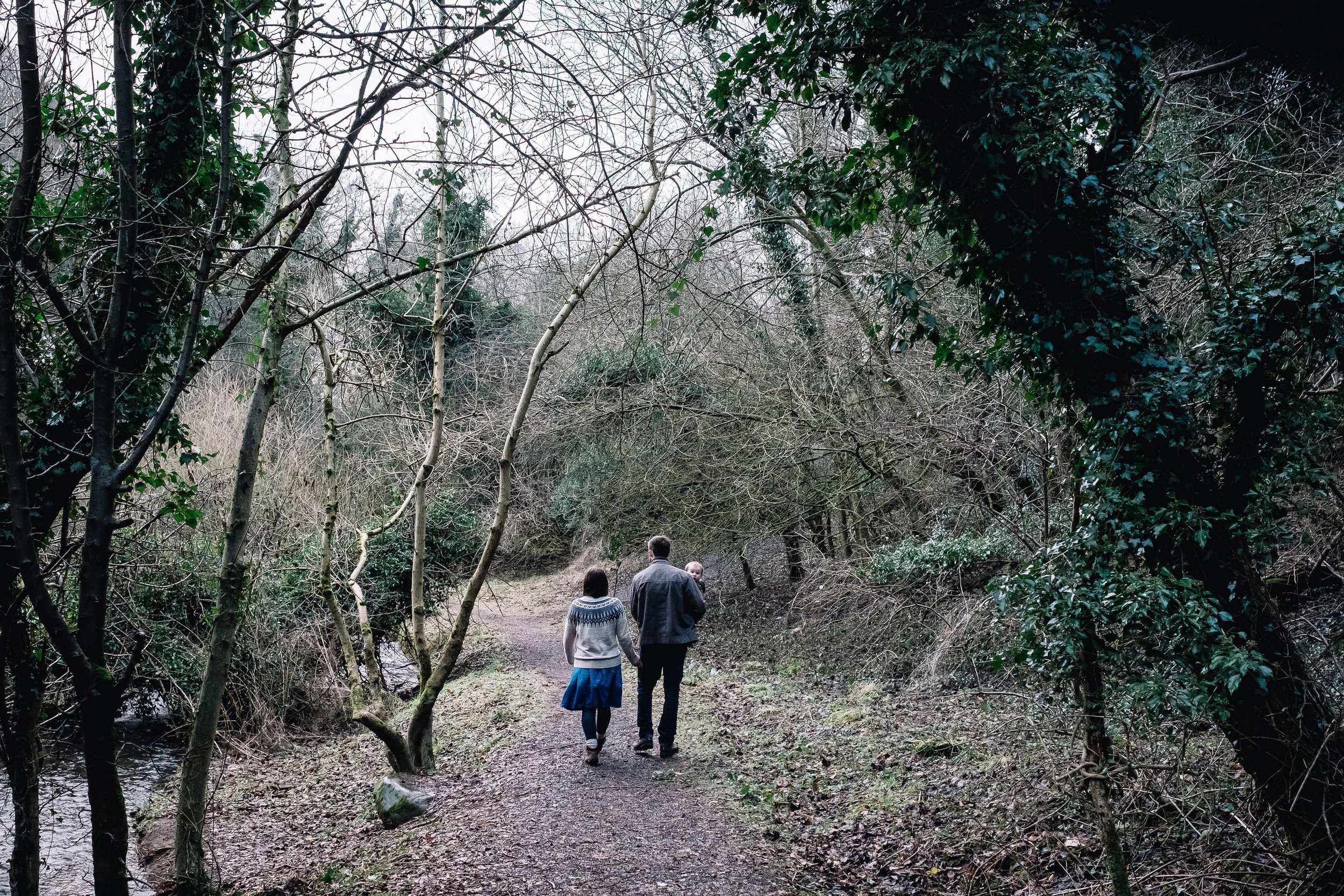 Family of three are walking in a forrest.