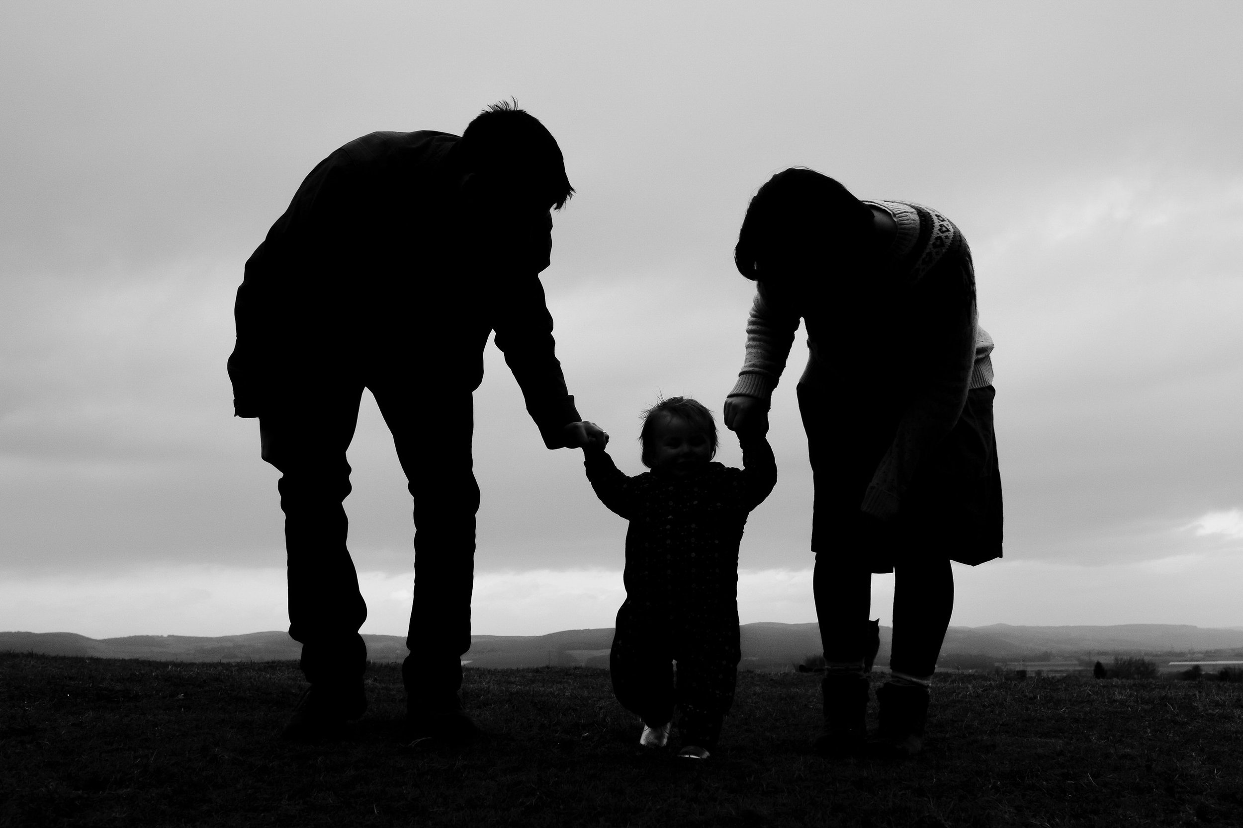 Family are silhoutted as they help their daugher to walk.