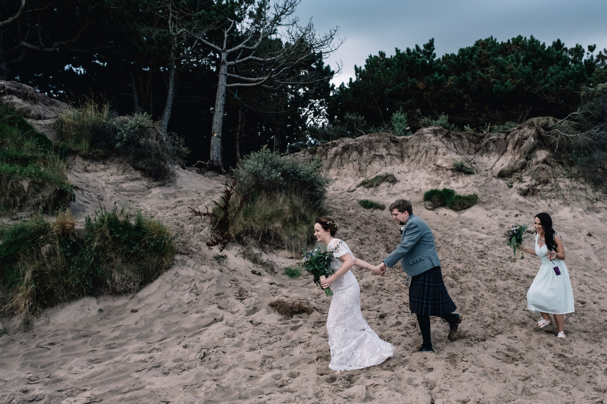 The bridal party make their way down to the beach for creative portraits